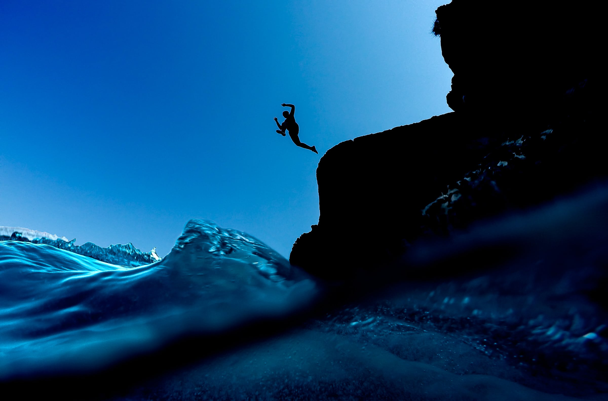 Man jumping in ocean near Red Sands Beach exploring Santorini Engagement photo ideas