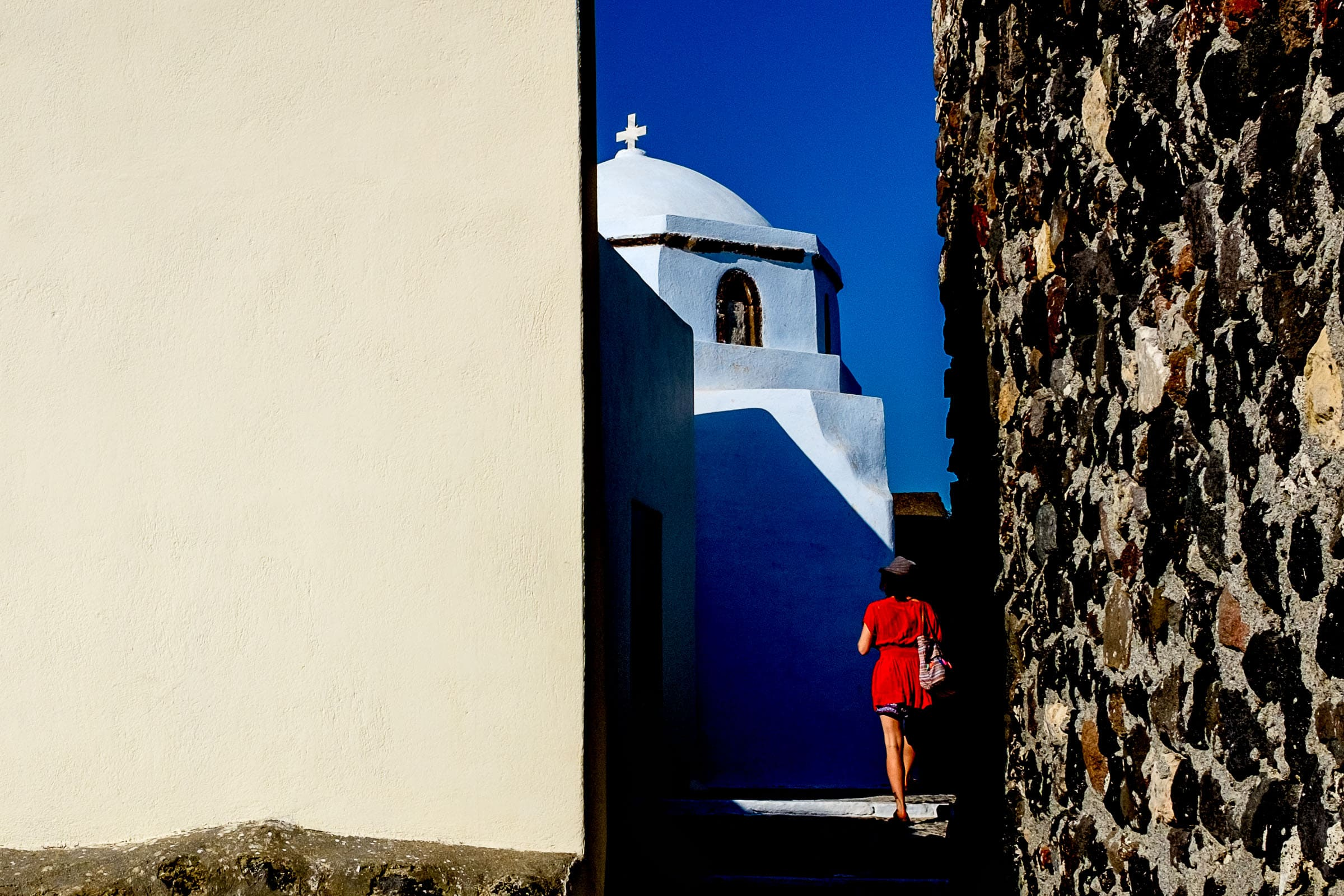 A woman in red walking through the back streets while exploring Santorini Engagement photo ideas