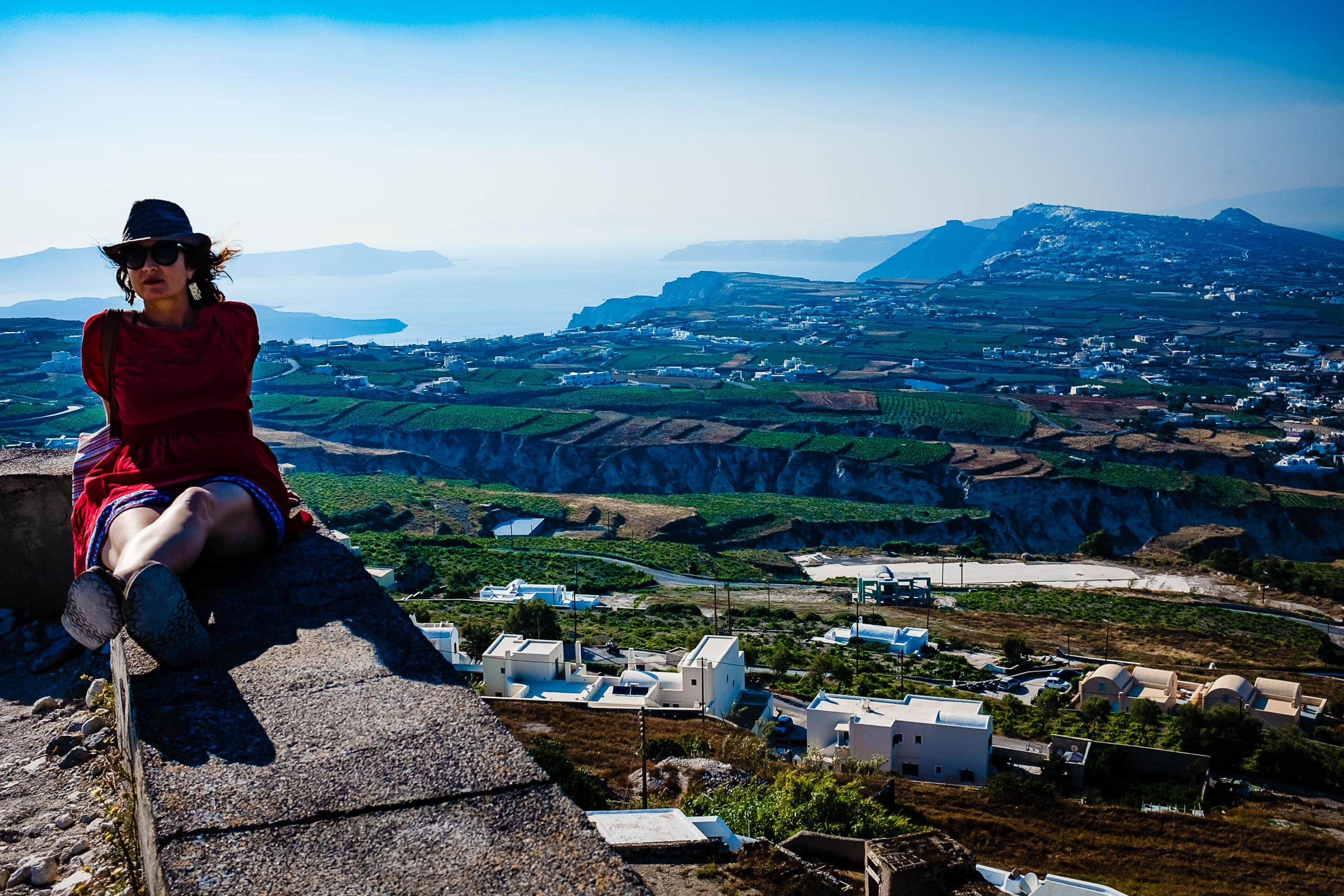 A woman sitting on a wall high up in Greece while exploring Santorini Engagement photo ideas