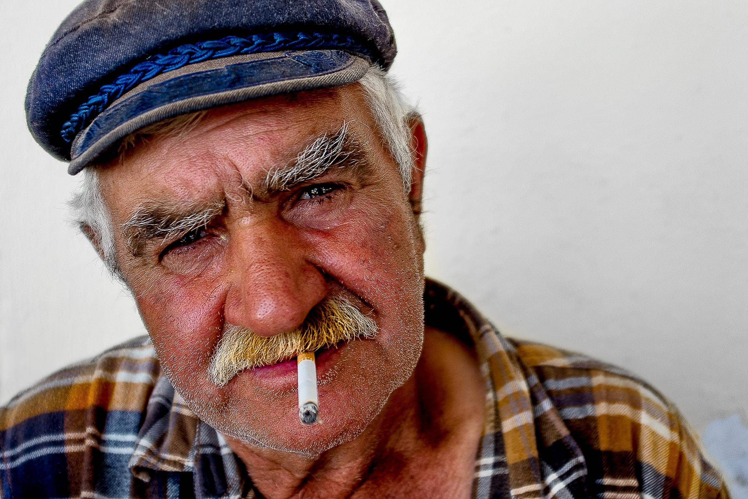 Portrait of an old man donkey caretaker in Greece while photographers explore Santorini Engagement photo ideas
