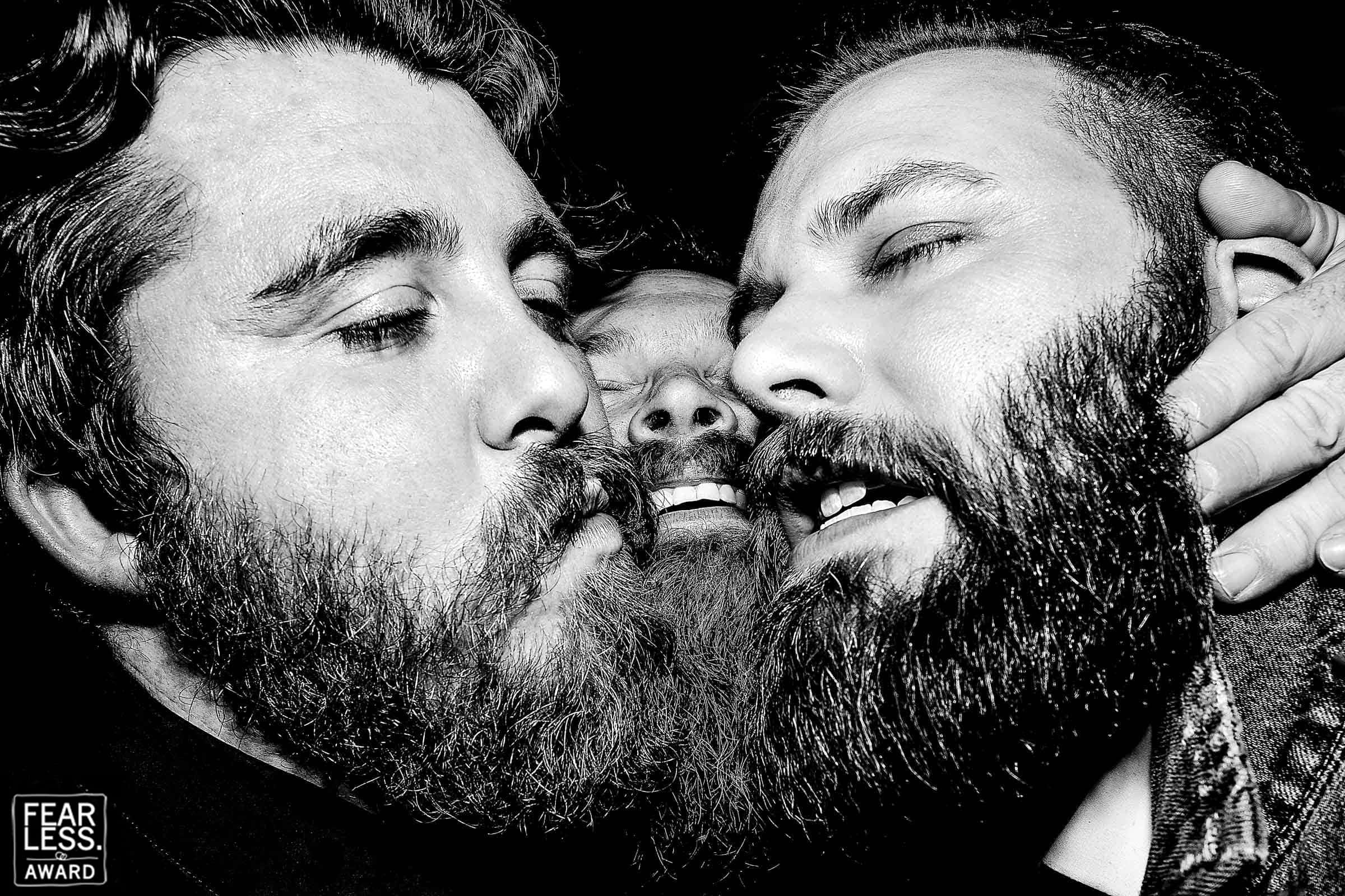 Three big bearded groomsmen with faces all scrunched together on the dance floor at a Los Angeles Wedding reception