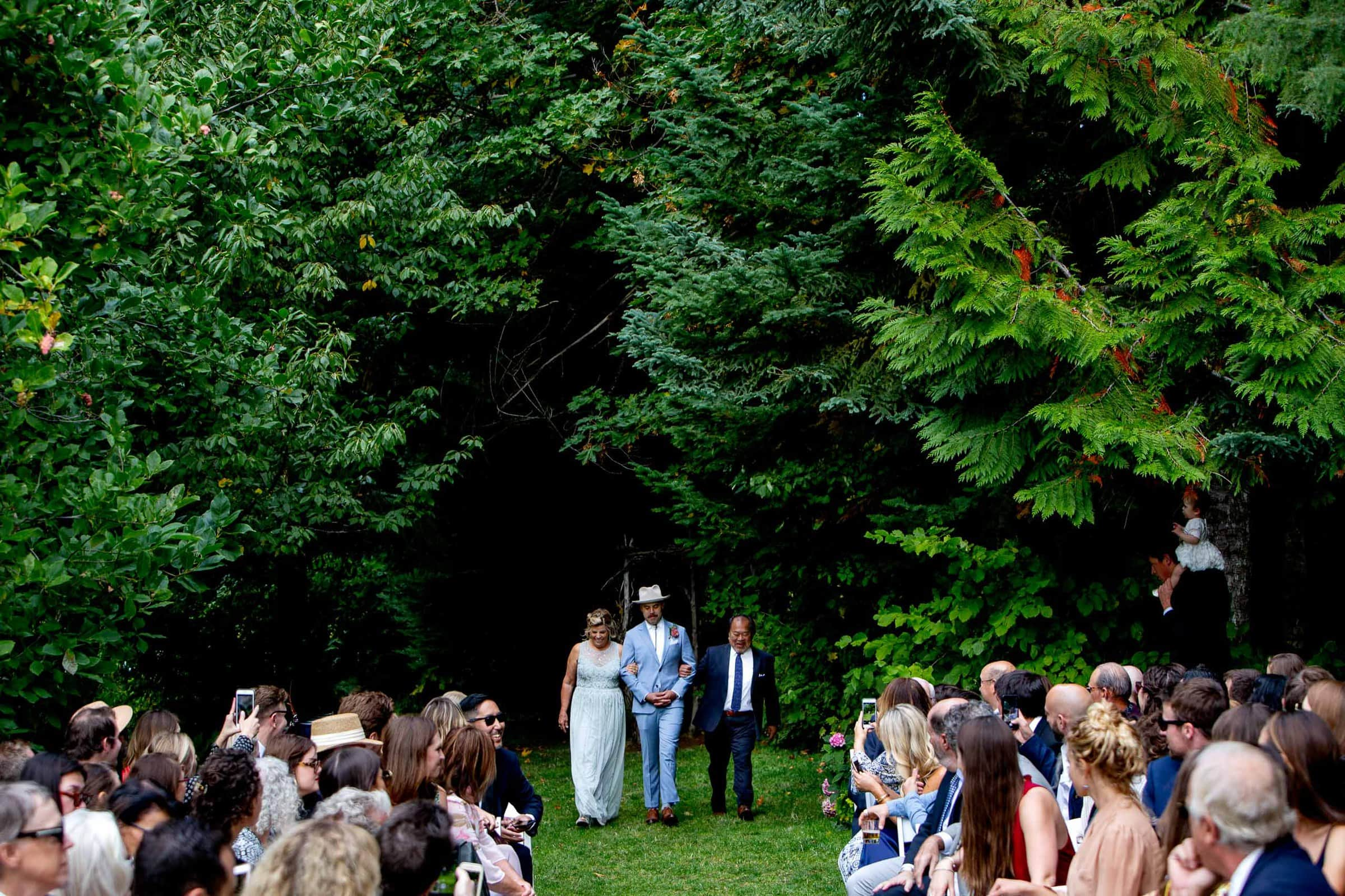 Groom walking into a Mt Hood Organic Farms wedding ceremony with parents