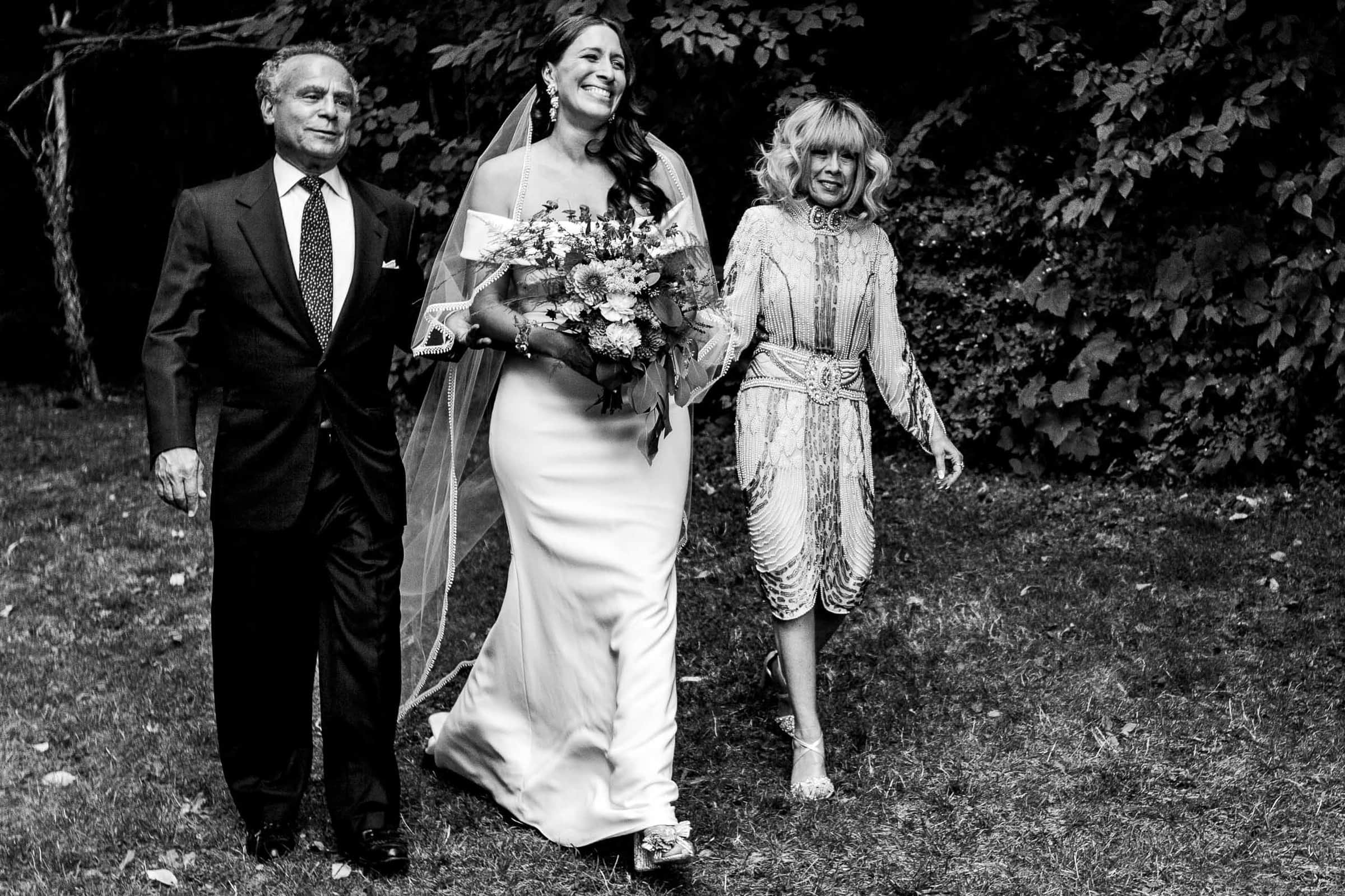 Bride walking into a Mt Hood Organic Farms wedding ceremony with parents