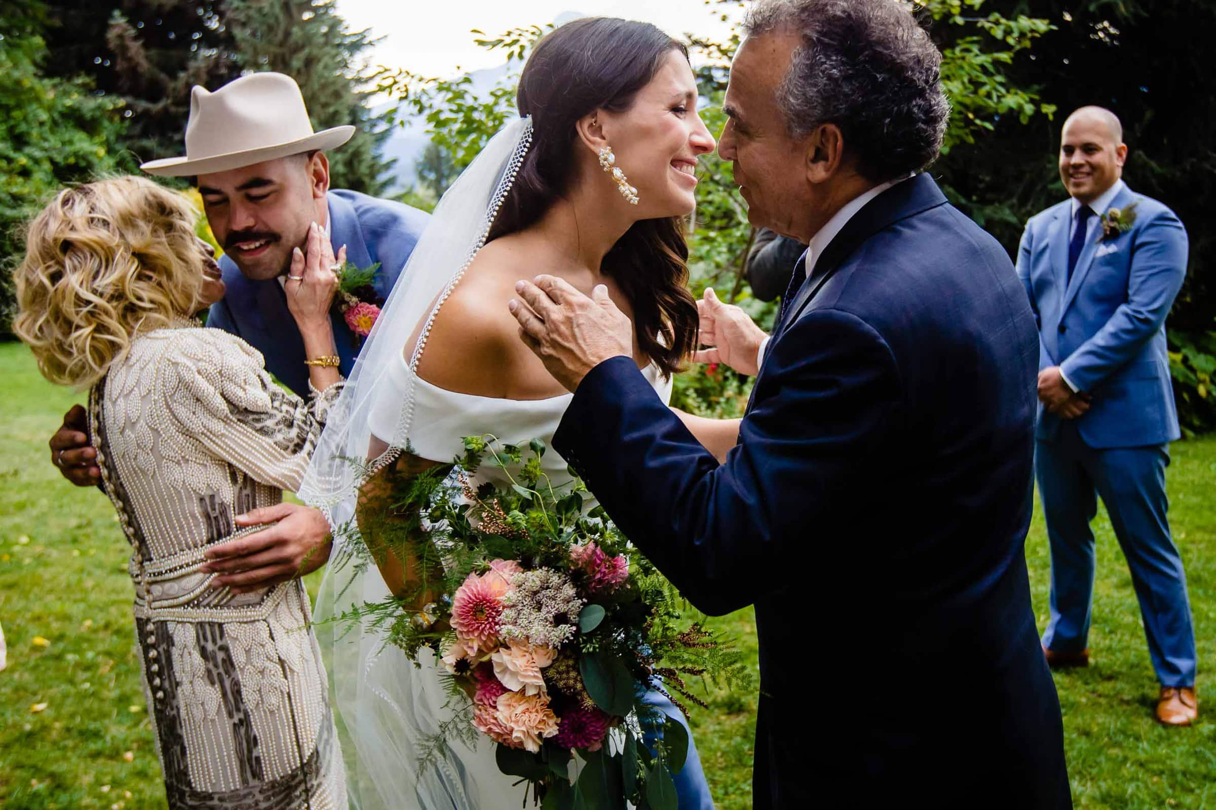 Bride and groom hugging parents while entering into a Mt Hood Organic Farms wedding ceremony with parents
