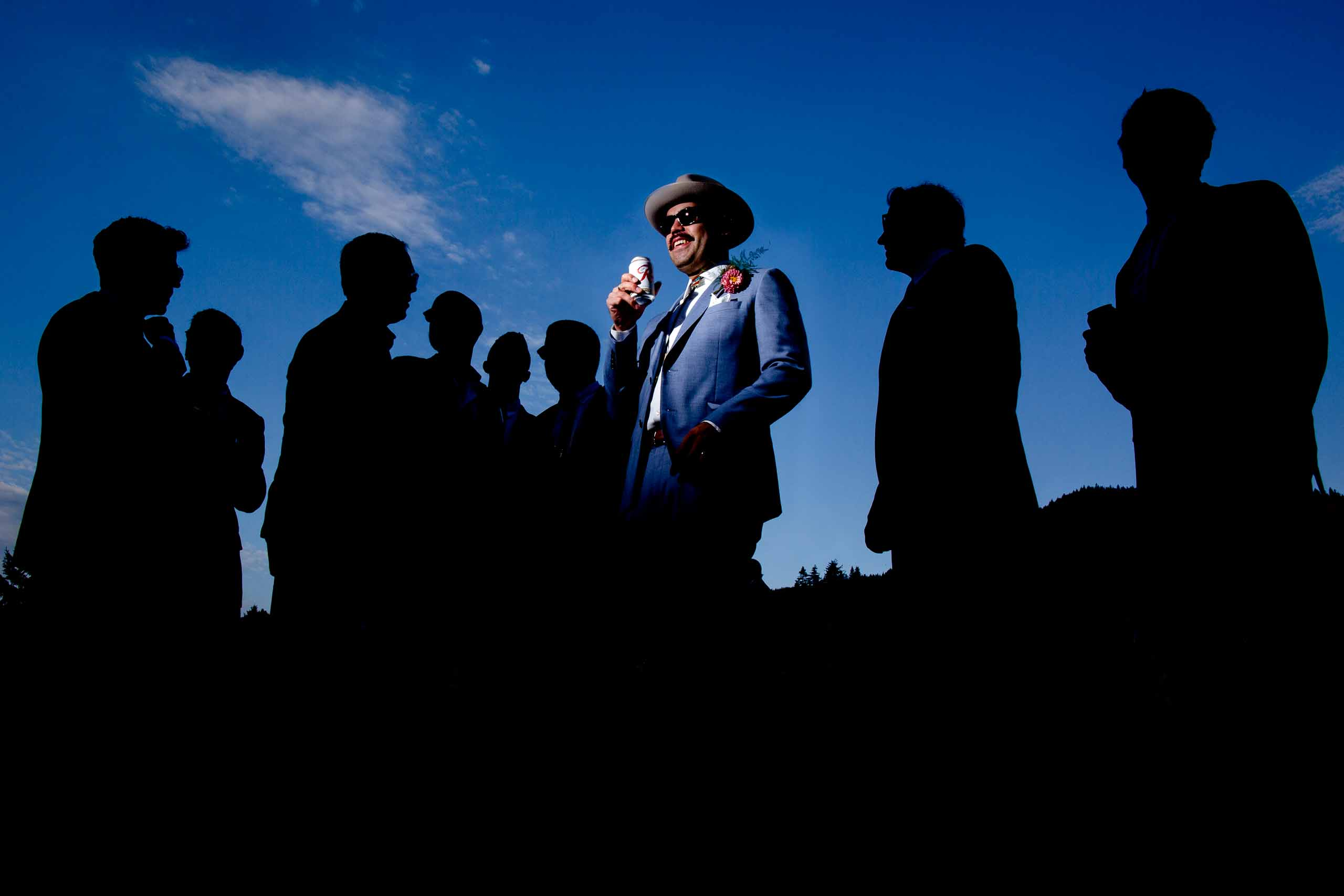 Epic photo of a groom lit up with his groomsmen silhouetted against the sky at the Mt Hood Organic Farms