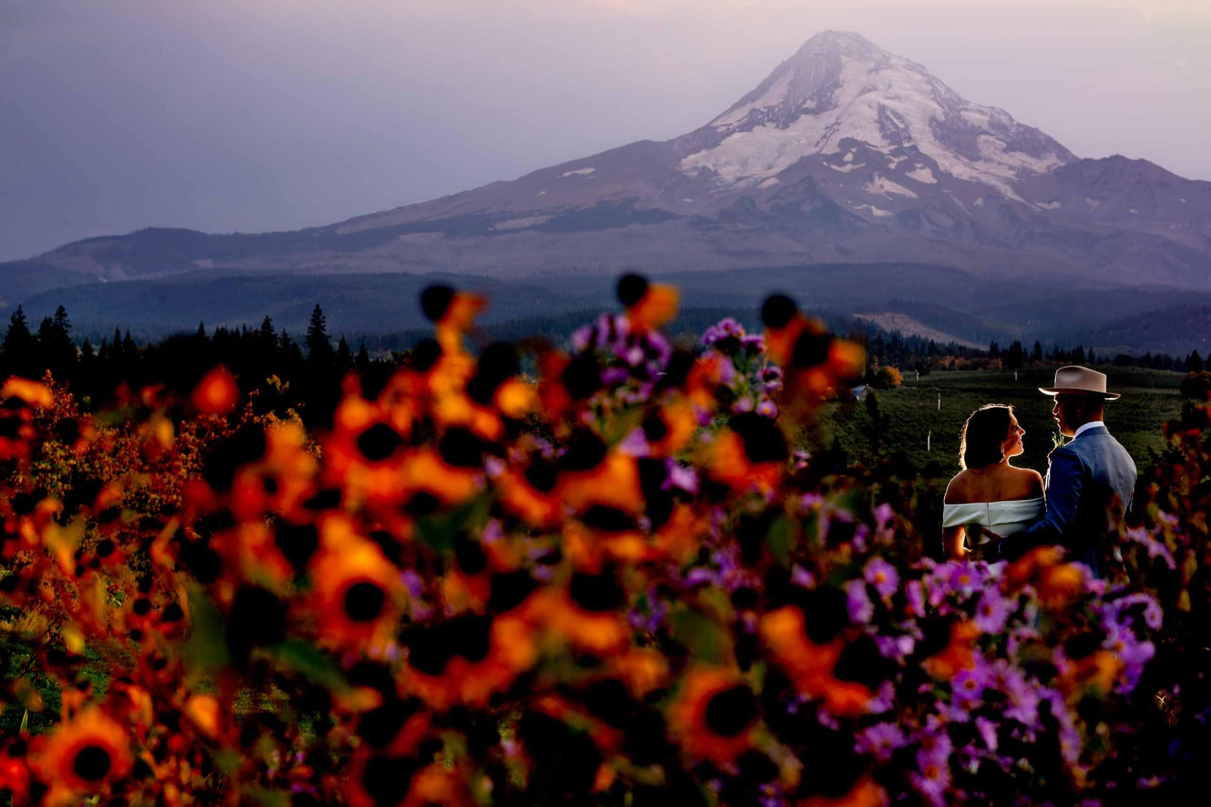 Bride and groom lit up at sunset with colorful flowers in the foreground at their Mt Hood Organic Farms wedding