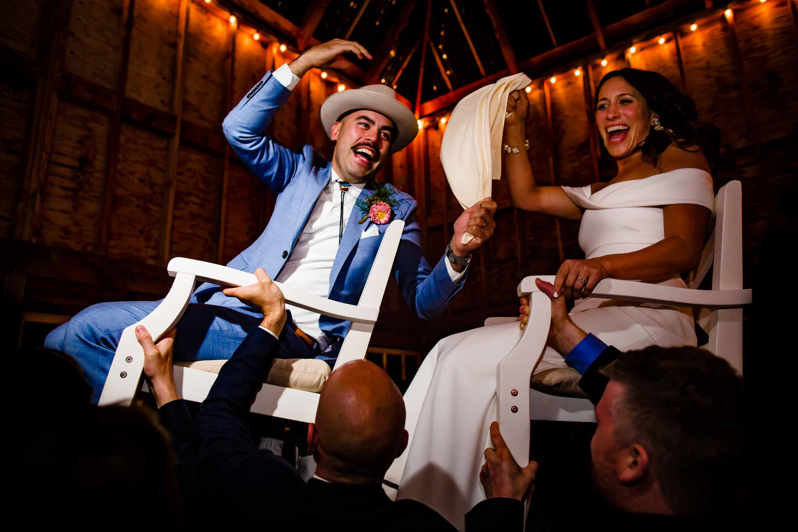 Groom and bride being carried by friends on a chair during his Mt Hood Organic Farms wedding reception