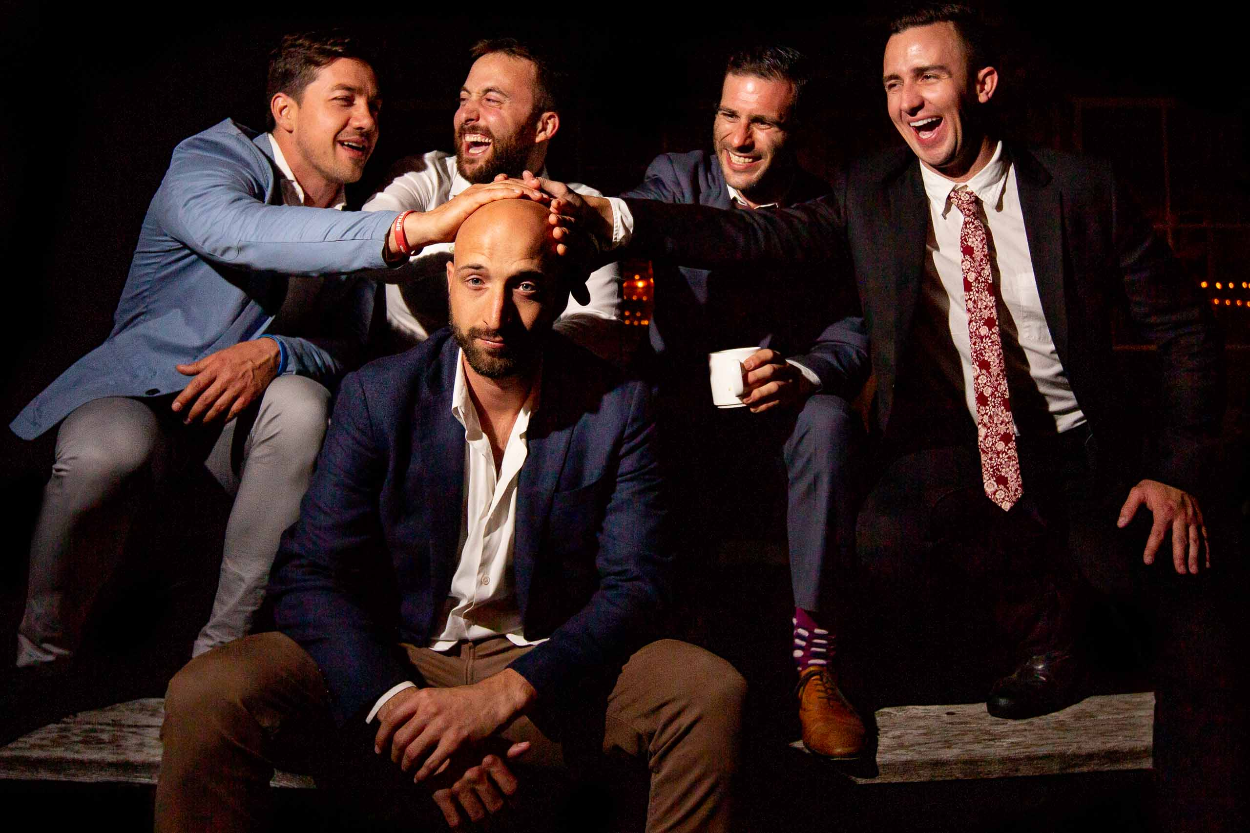 Fun friends playing with a groomsmen bald head at a Mt Hood Organic Farms wedding reception