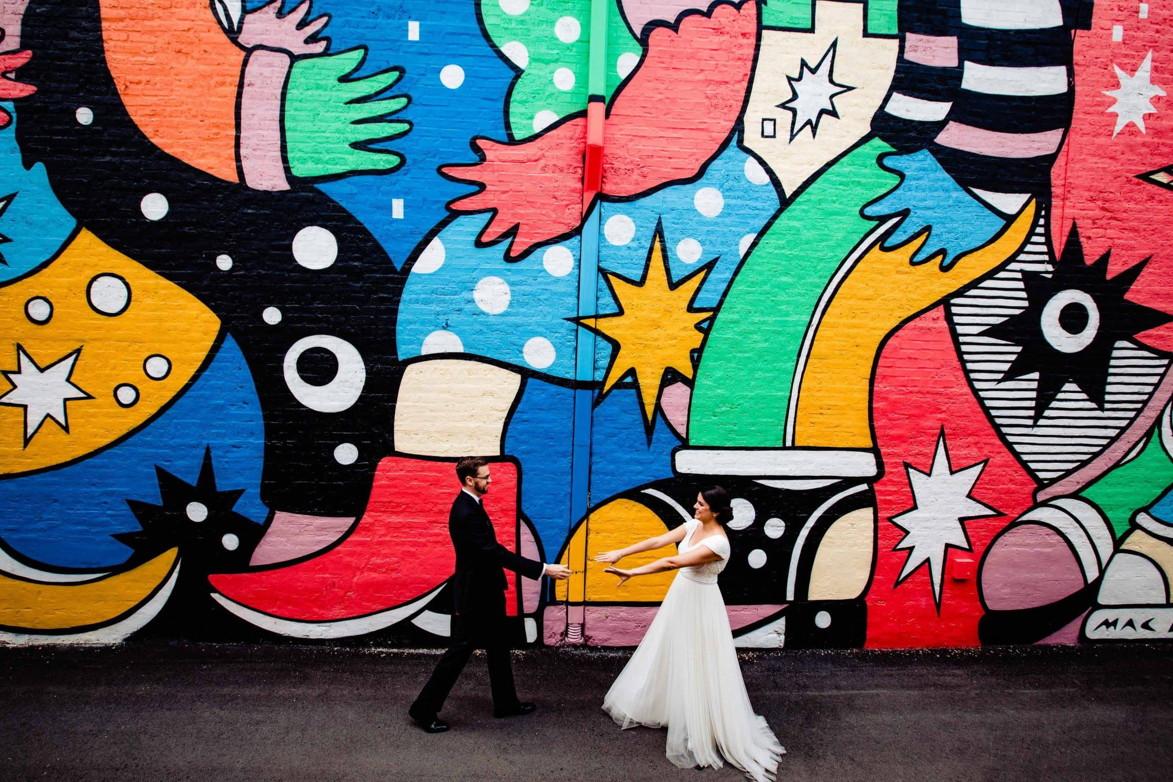 Creative photo of a bride and groom seeing each other with a massive mural before their Cafe Brauer Wedding in Chicago, Illinois