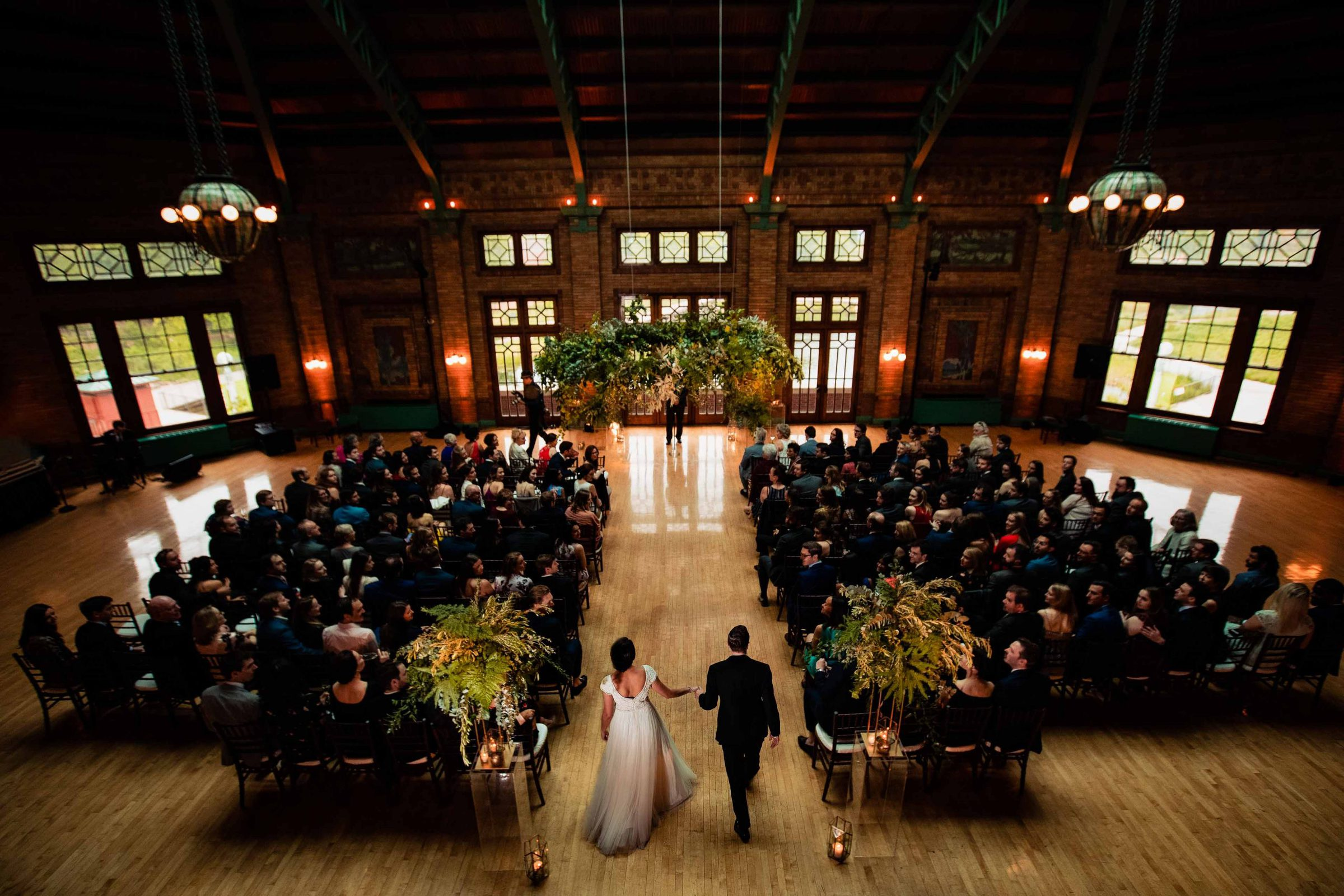 Epic entrance photo of a bride and groom walking into their wedding ceremony at Cafe Brauer in Chicago, Illinois.