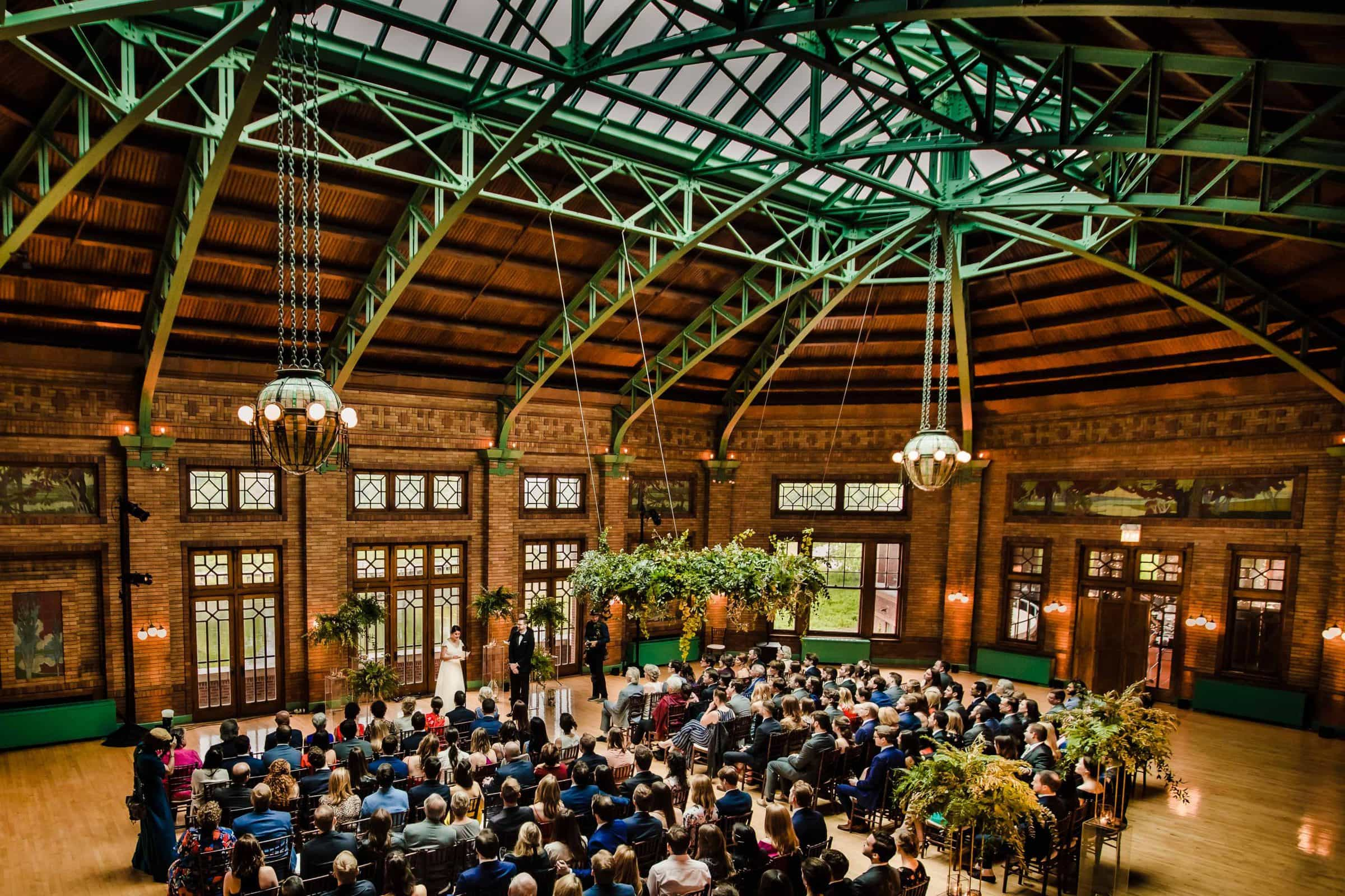 Epic photo of a bride and groom exchanging vows during their wedding ceremony at Cafe Brauer in Chicago, Illinois.