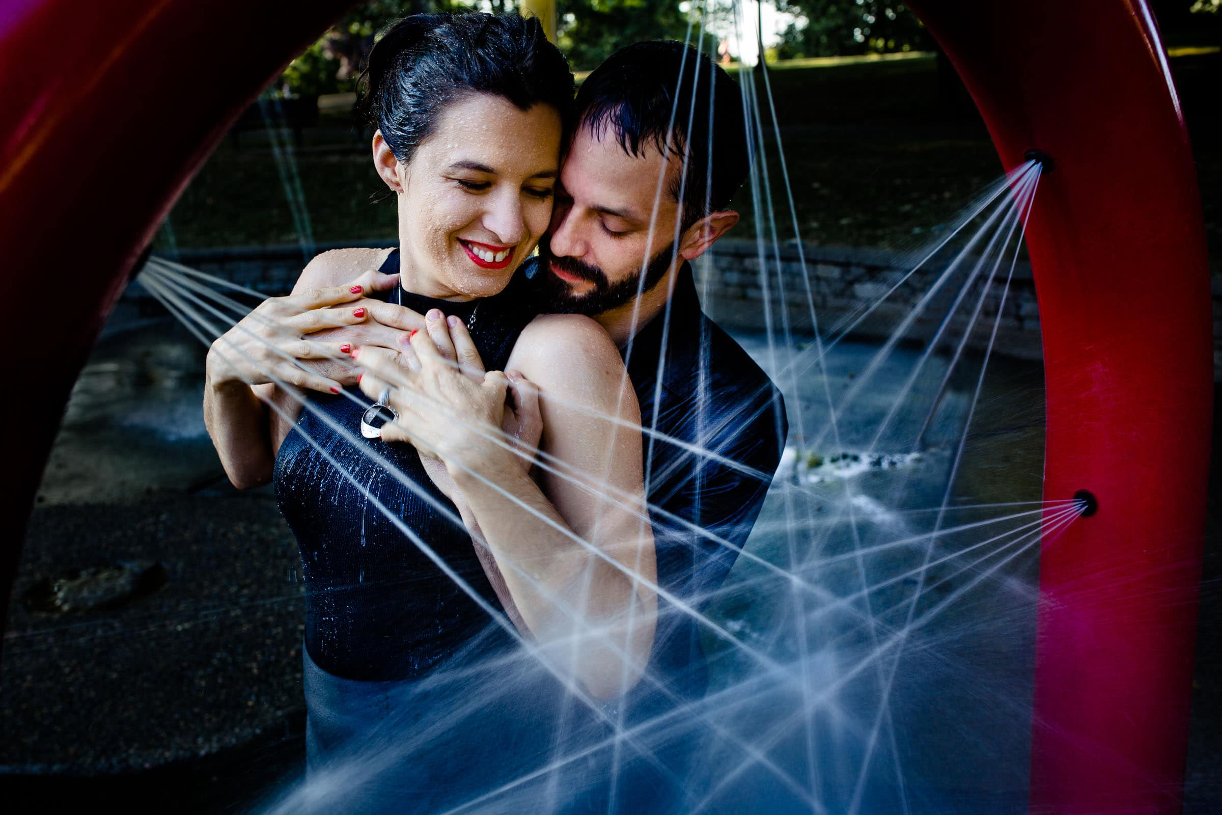 Creative Portland engagement photos of a couple being showered in a fountain