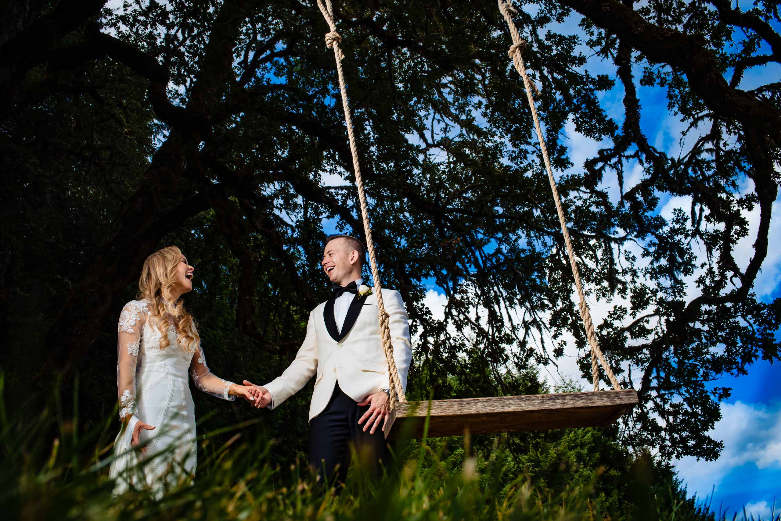 Bride and groom playing on a swing before their Youngberg Hill Wedding