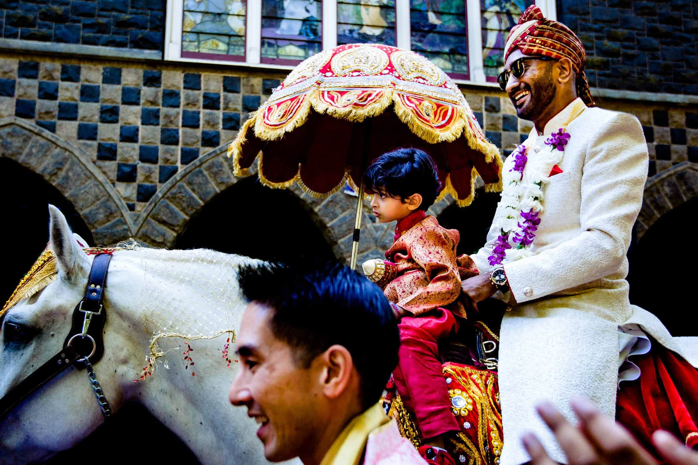 Indian groom riding white horse in the Baraat during a Portland Art Museum wedding