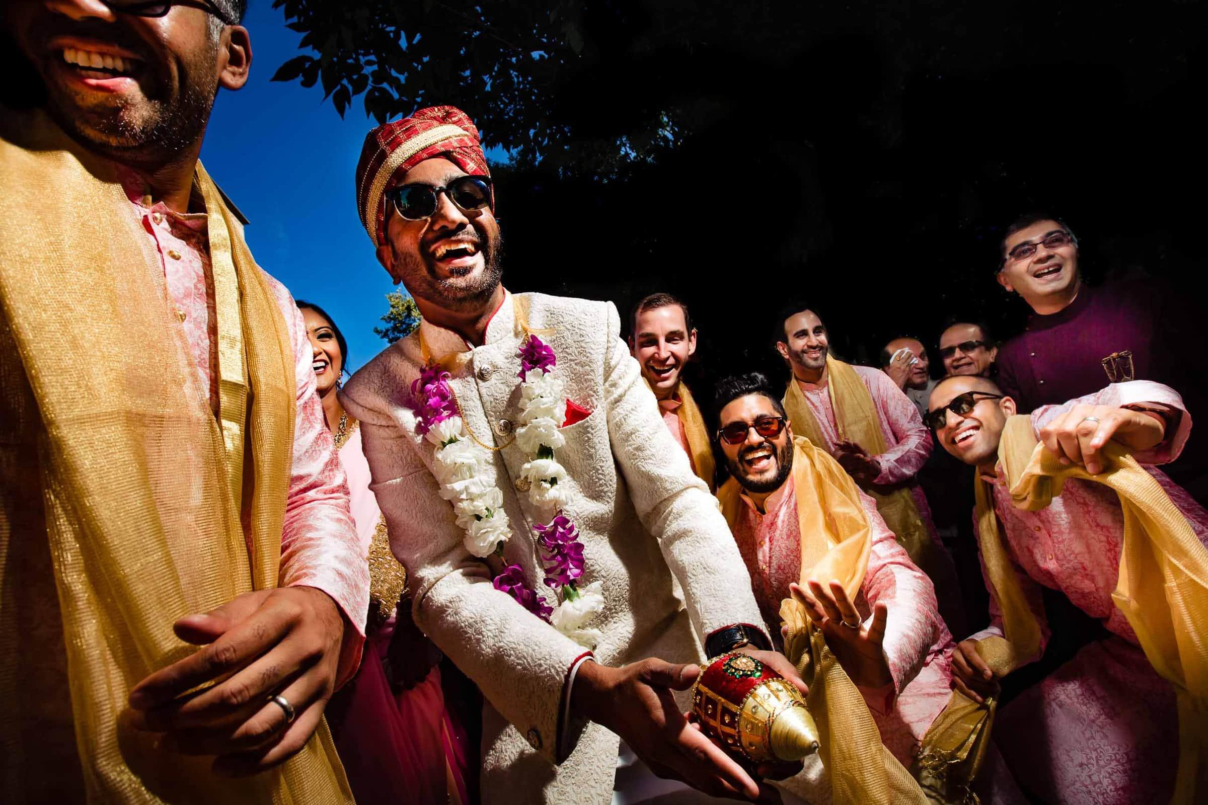 Indian groomsmen dancing while in the baraat during a big Portland Art Museum wedding