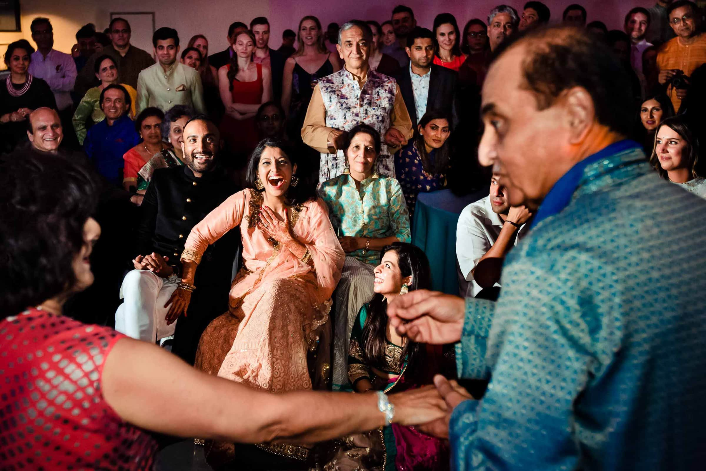 Bride and groom laughing during the Sangeet the day before their Portland Art museum wedding.