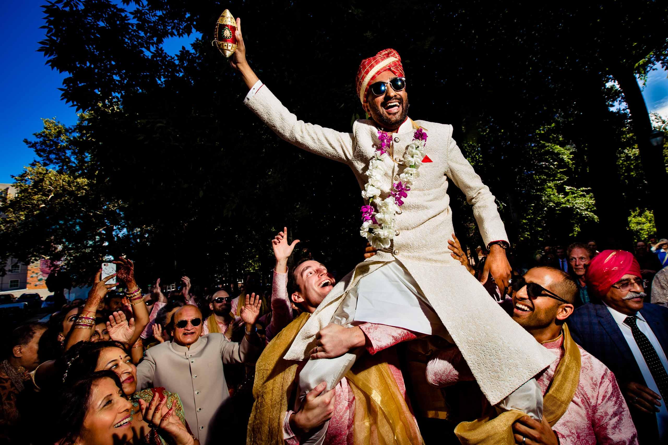 Indian groom riding on groosmens shoulders at a big Indian Portland Art Museum wedding