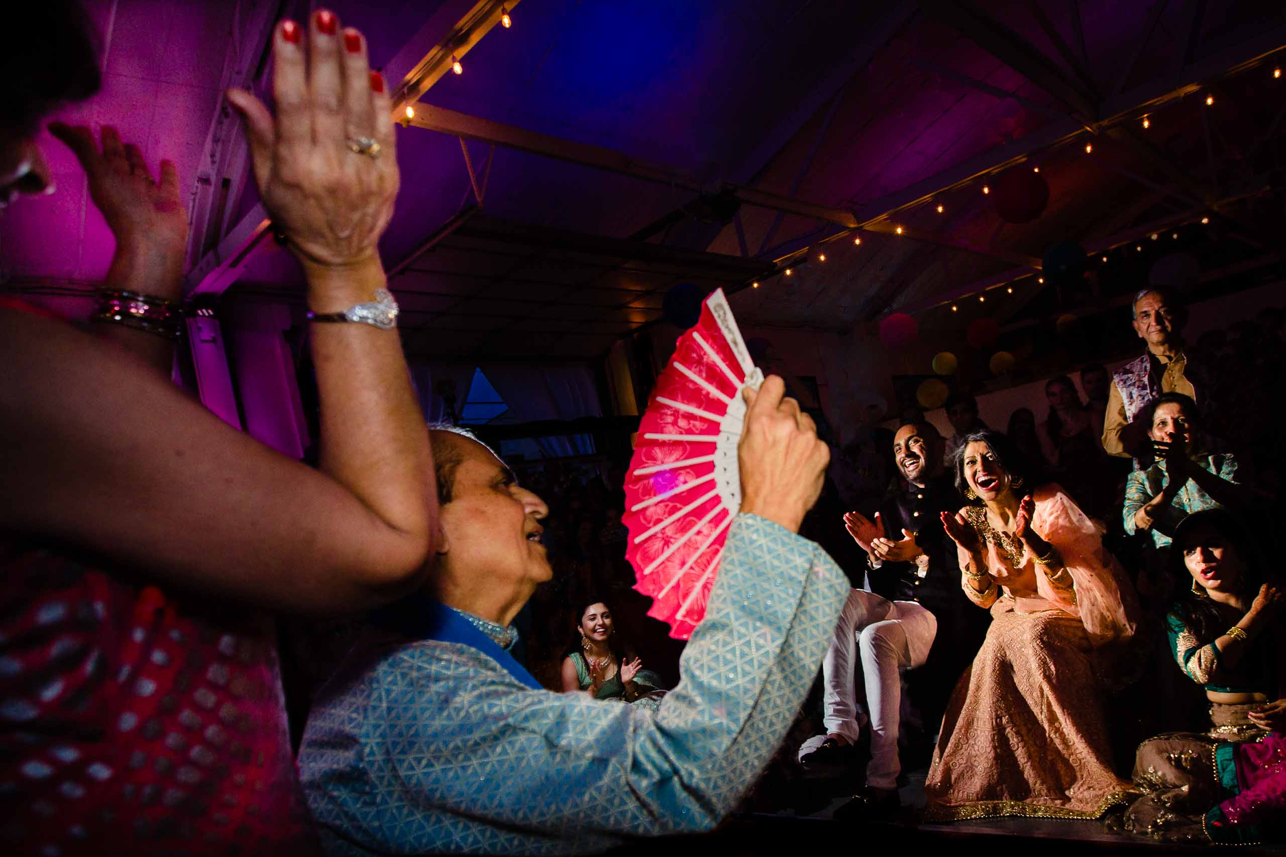 Super creative photo of Indian bride and groom laughing while parents perform during the Sangeet before their Portland Art Museum wedding.
