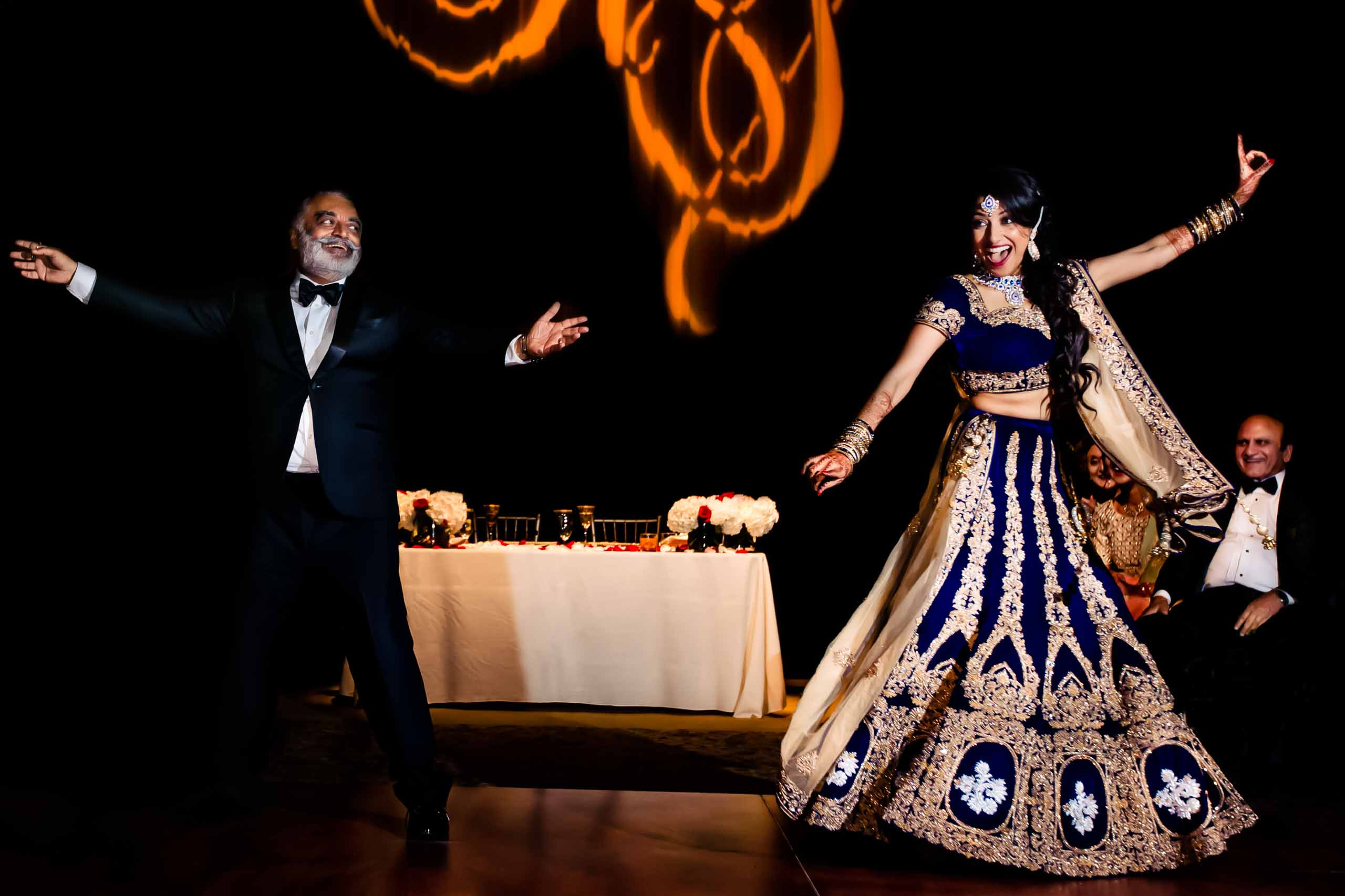 Exciting photo of an Indian bride and her father dancing during a Portland Art museum wedding.