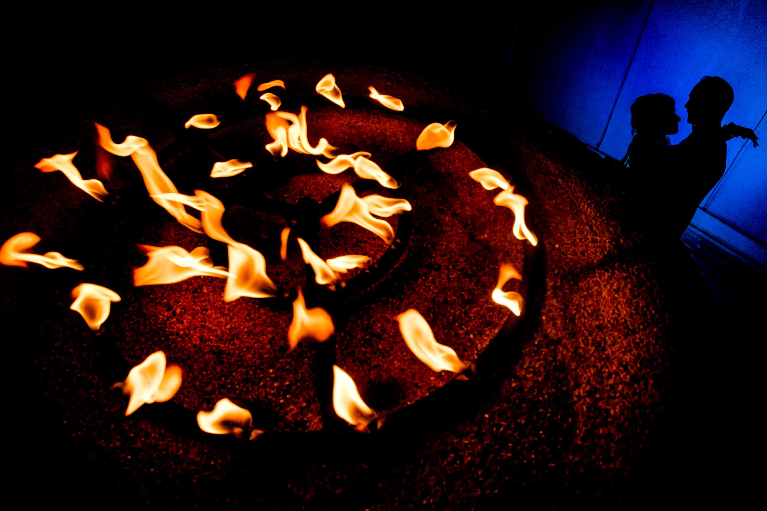 Extremely creative photo of an Indian bride and groom near fire flames at their Portland Art museum wedding.