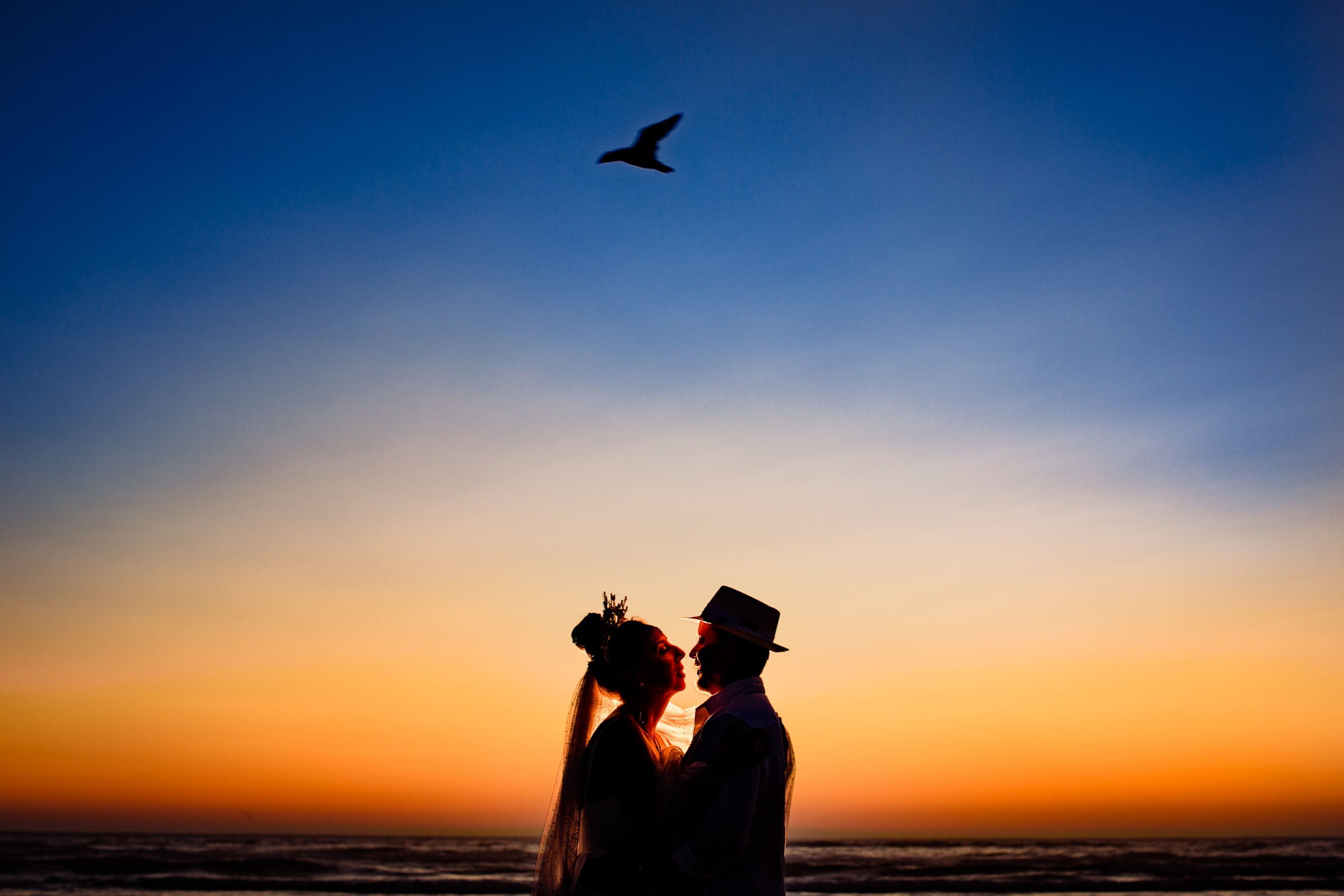 Gorgeous sunset wedding portrait of bride and groom near Haystack Rock with bird flying over head