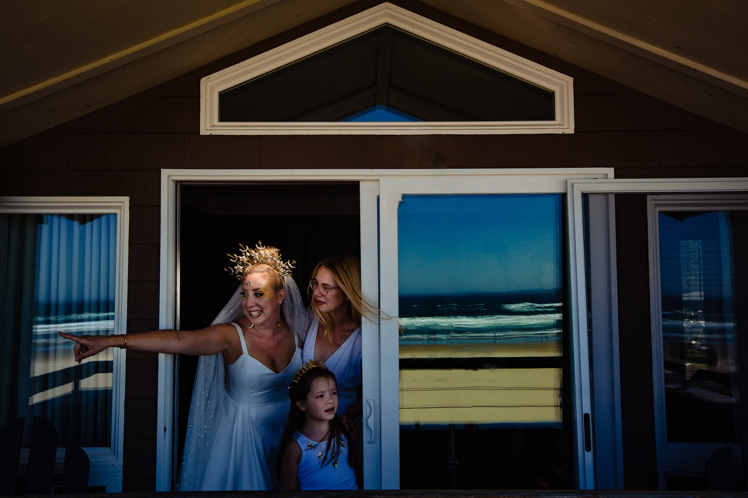 A fun moment of a bride and her best friend and daughter while getting ready for a Cannon Beach wedding