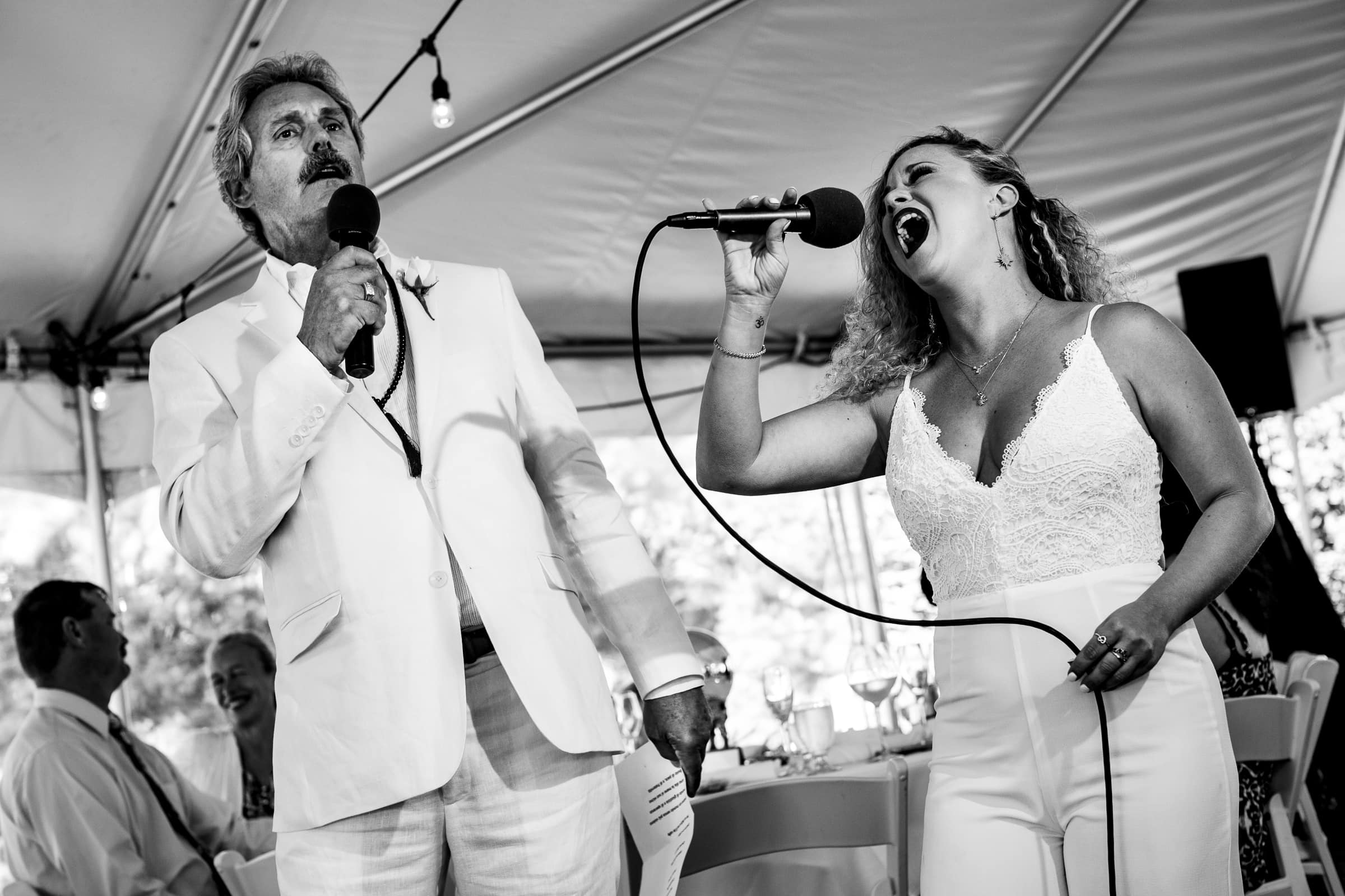 A dramatic photo of a woman and man singing Andrea Bocelli song during a Cannon Beach wedding reception near Haystack Rock in Oregon
