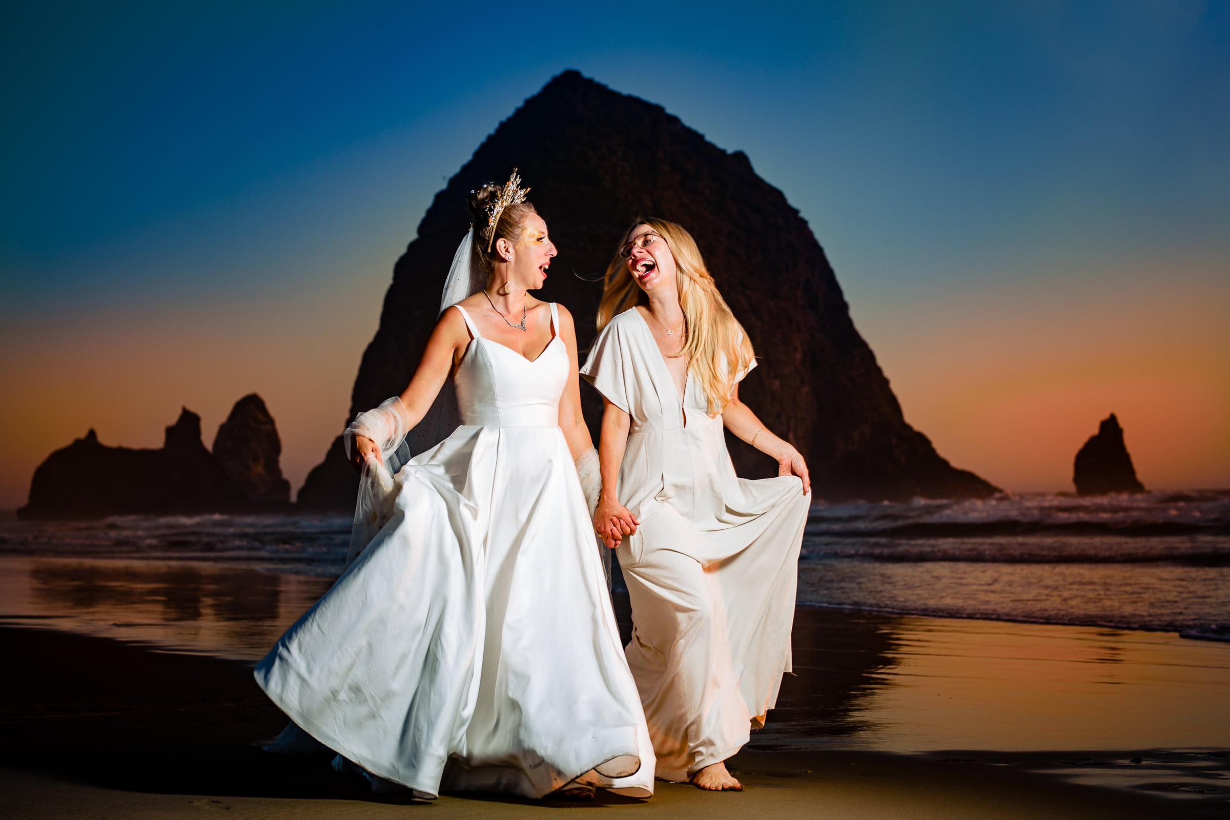 A beautifully lit up photo of a bride and her best friend walking infront of Haystack Rock for a Cannon Beach Wedding in Oregon