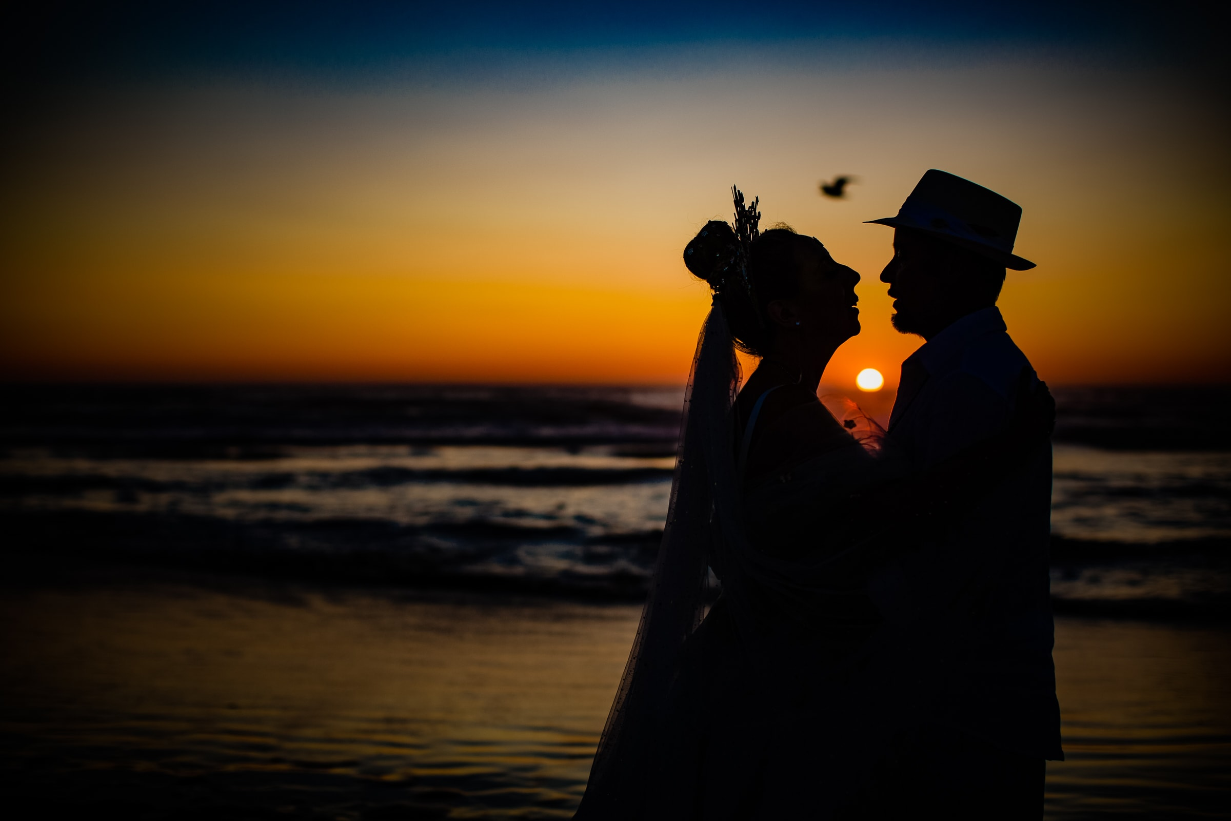 An exquisite silhouette photo of a bride and groom at sunset near Haystack Rock during their Cannon Beach Wedding in Oregon