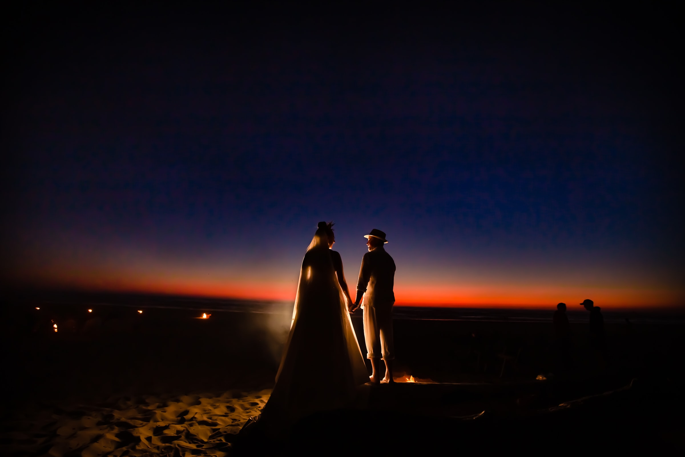 An beautifully back lit photo of a bride and groom at sunset near Haystack Rock during their Cannon Beach Wedding in Oregon