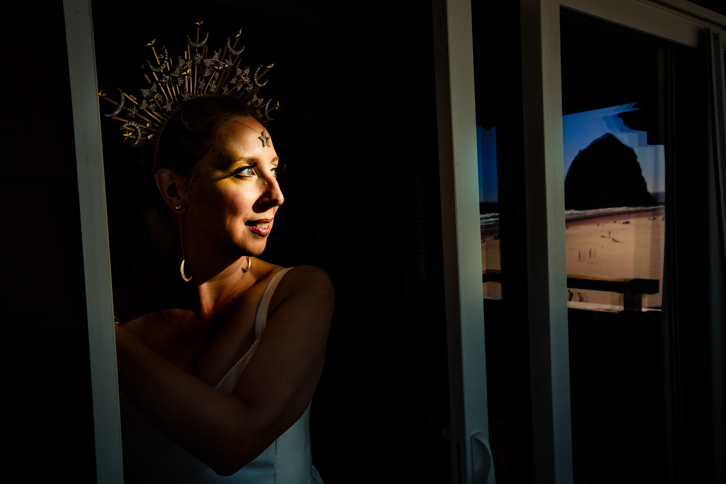 A dramatic portrait of a bride in a doorway with Haystack Rock in the distance while getting ready for a Cannon Beach wedding