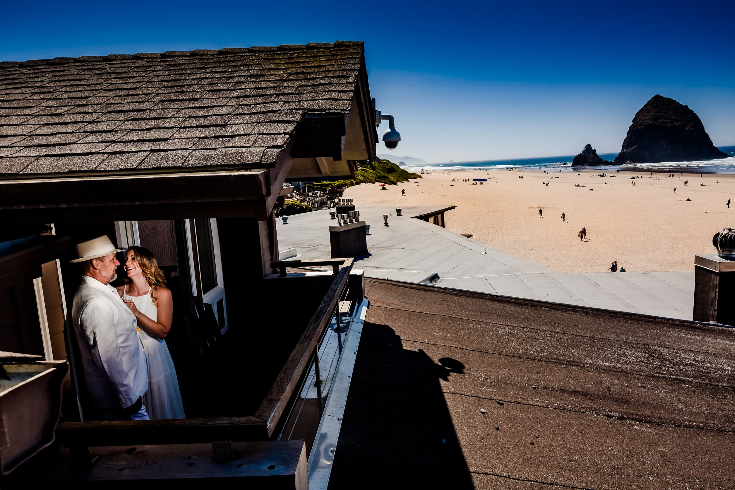 A photo of a groom getting ready with his best lady with Haystack Rock in the distance while getting ready for a Cannon Beach wedding