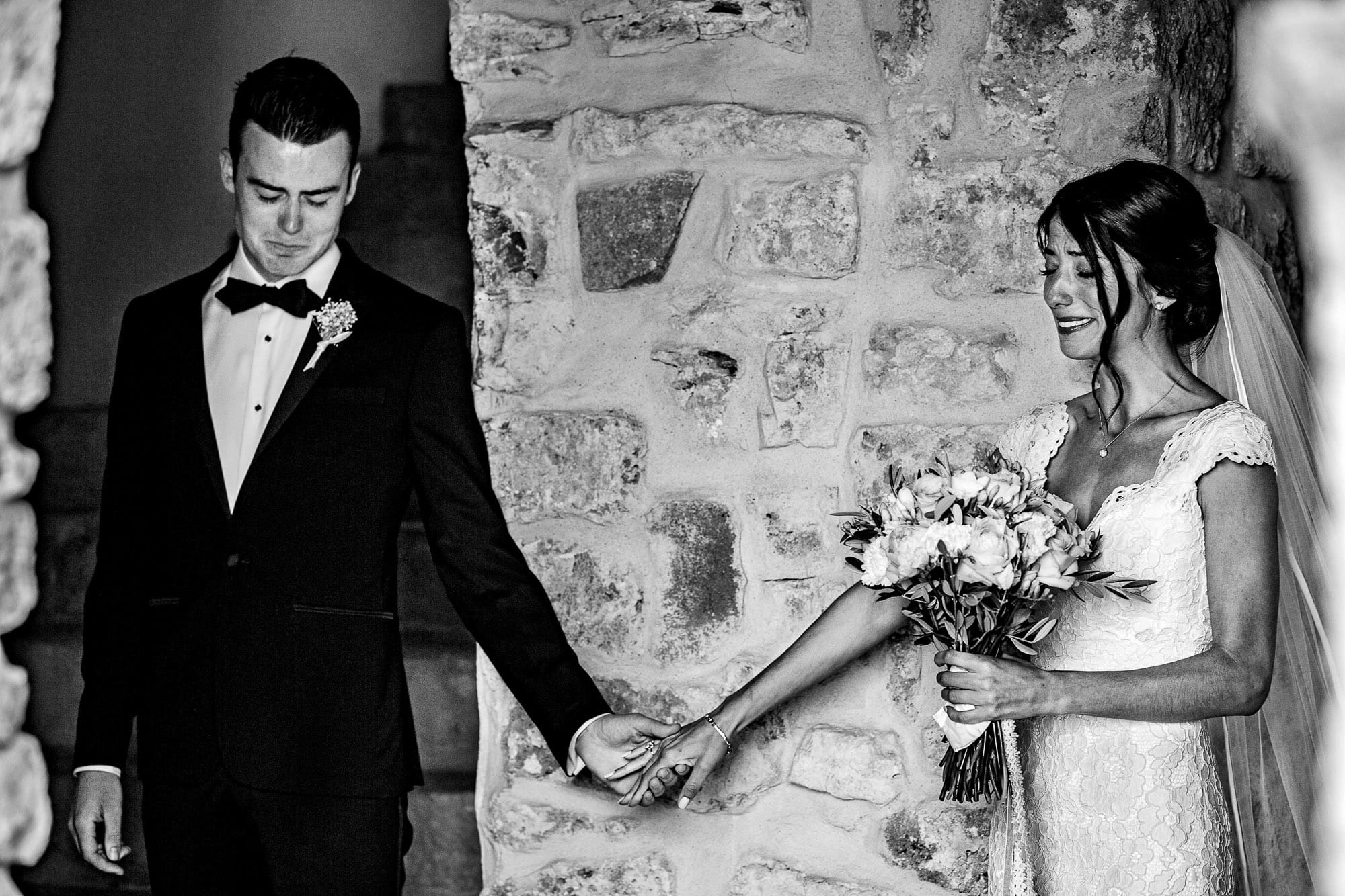 Emotional moment of bride and groom touching hands without looking before their Chateau Zen wedding ceremony in the South of France.
