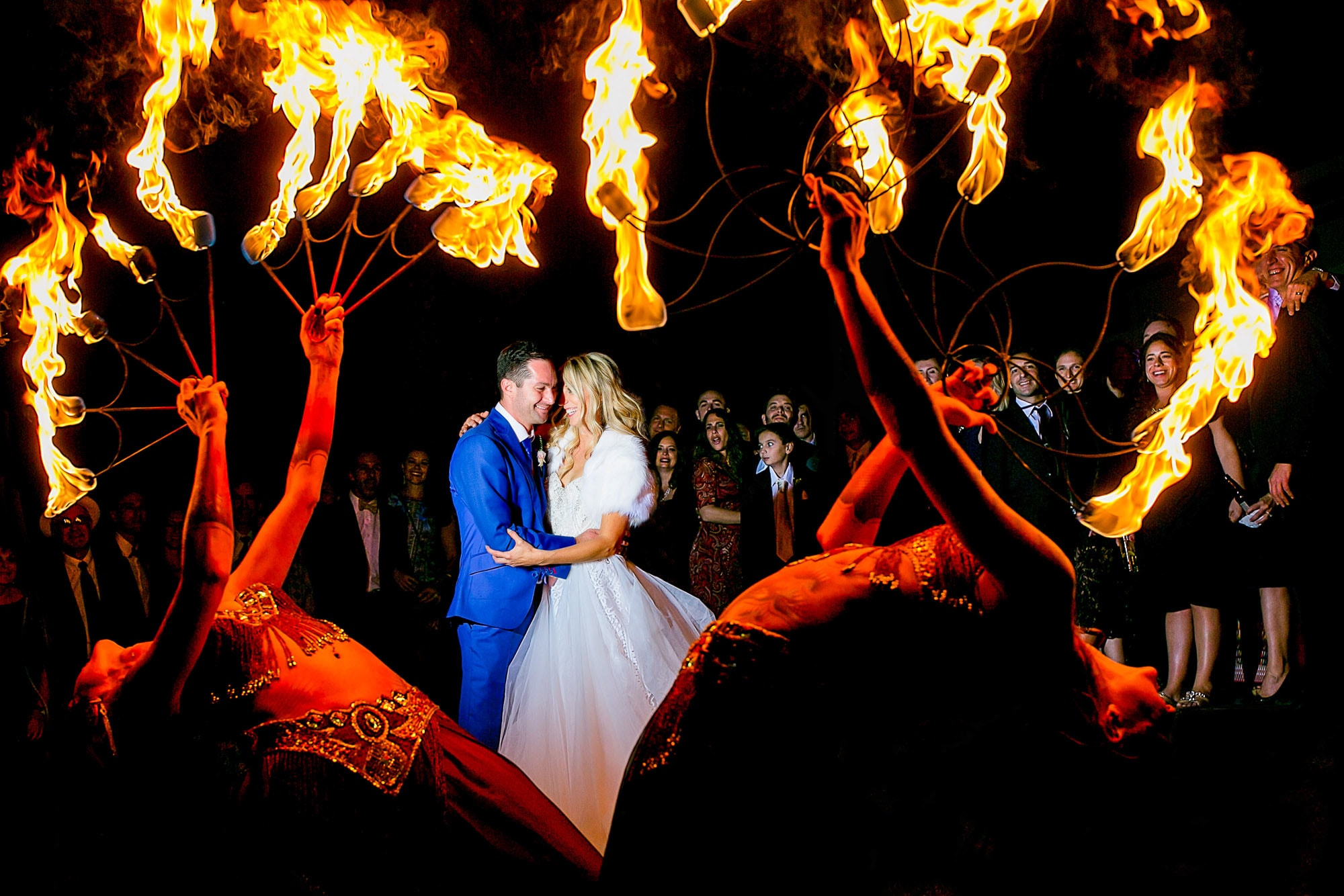 Bride and Groom seen through circus performers with heart shaped flame fearless photographers award winning photo