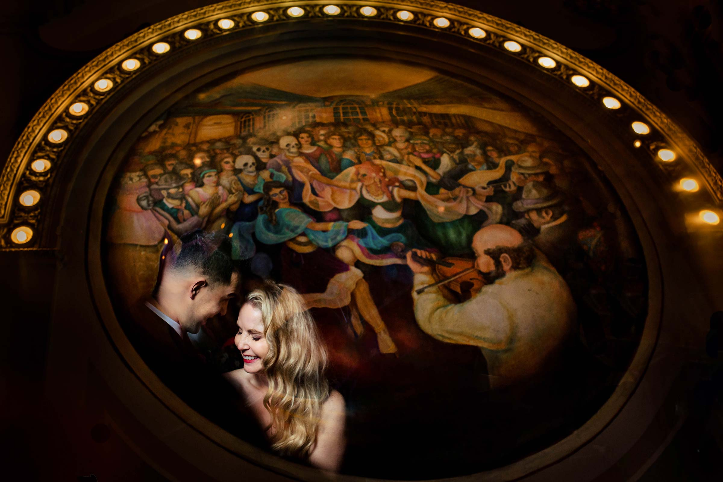 Creative photo of bride and groom reflected in a mural painting at the famous Crystal Ballroom after their First Presbyterian Church Wedding in Portland Oregon