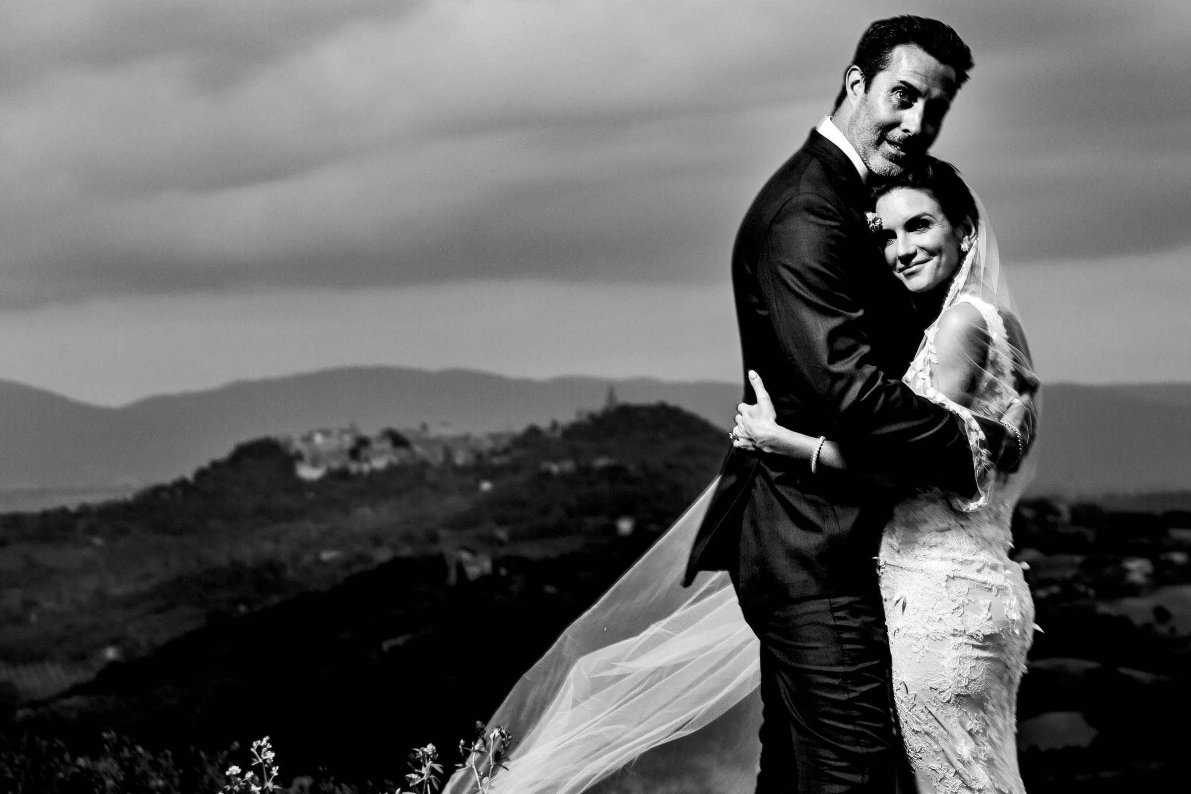 Bride and groom embracing together with the view from Villa Tre Grazie wedding celebration near Todi, Italy.