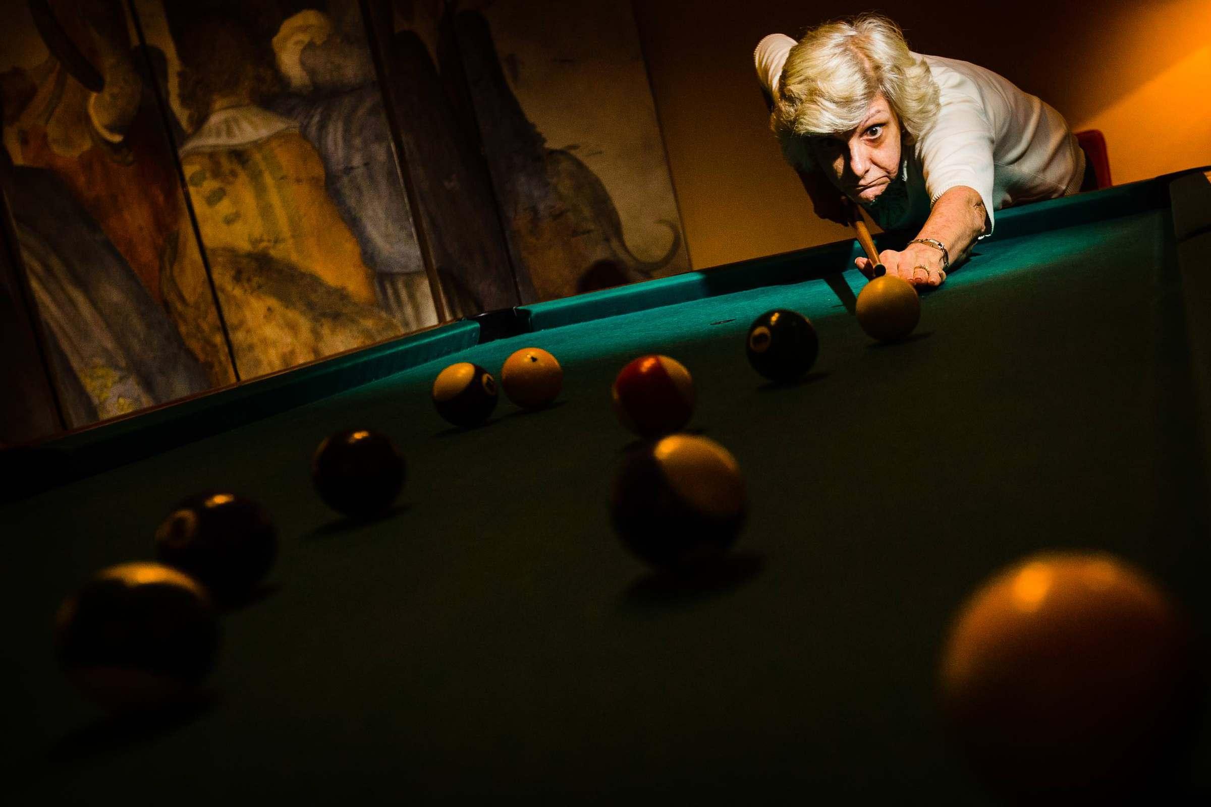 Mother enjoying playing pool during a Villa Tre Grazie wedding celebration near Todi, Italy.