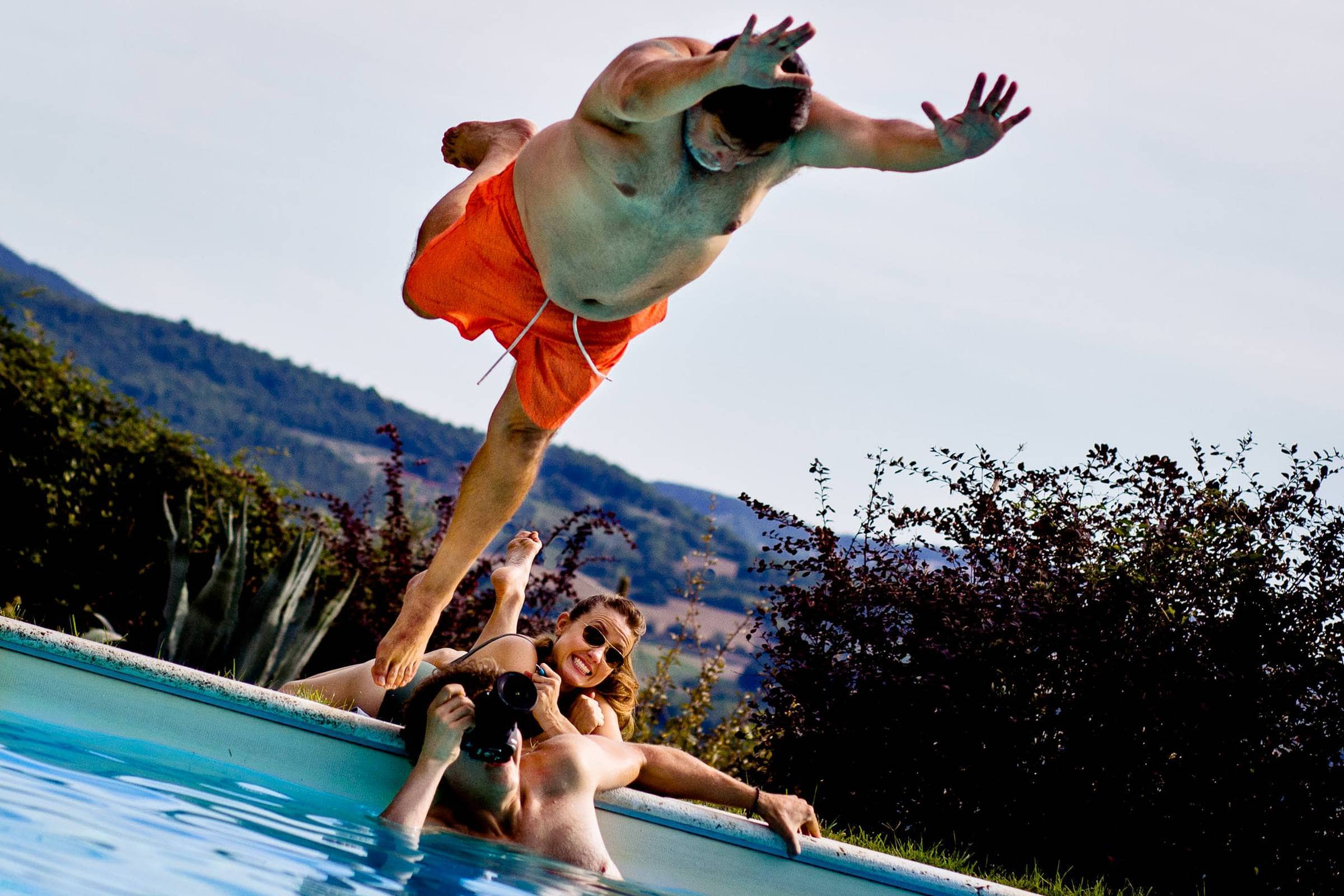 Guest diving into a pool party during a Villa Tre Grazie wedding celebration near Todi, Italy.