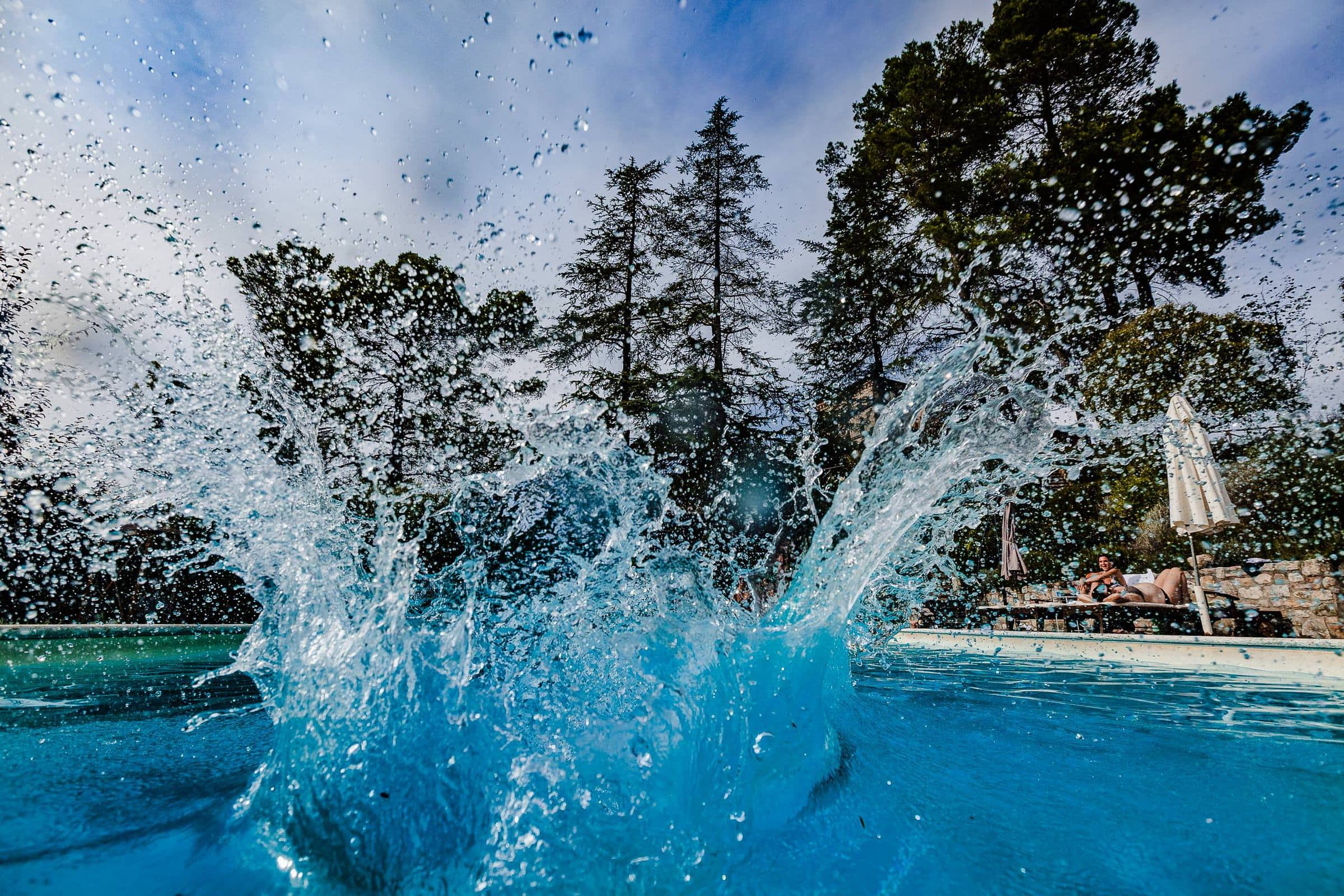 Guest doing a massive cannon ball at a pool party during a Villa Tre Grazie wedding celebration near Todi, Italy.
