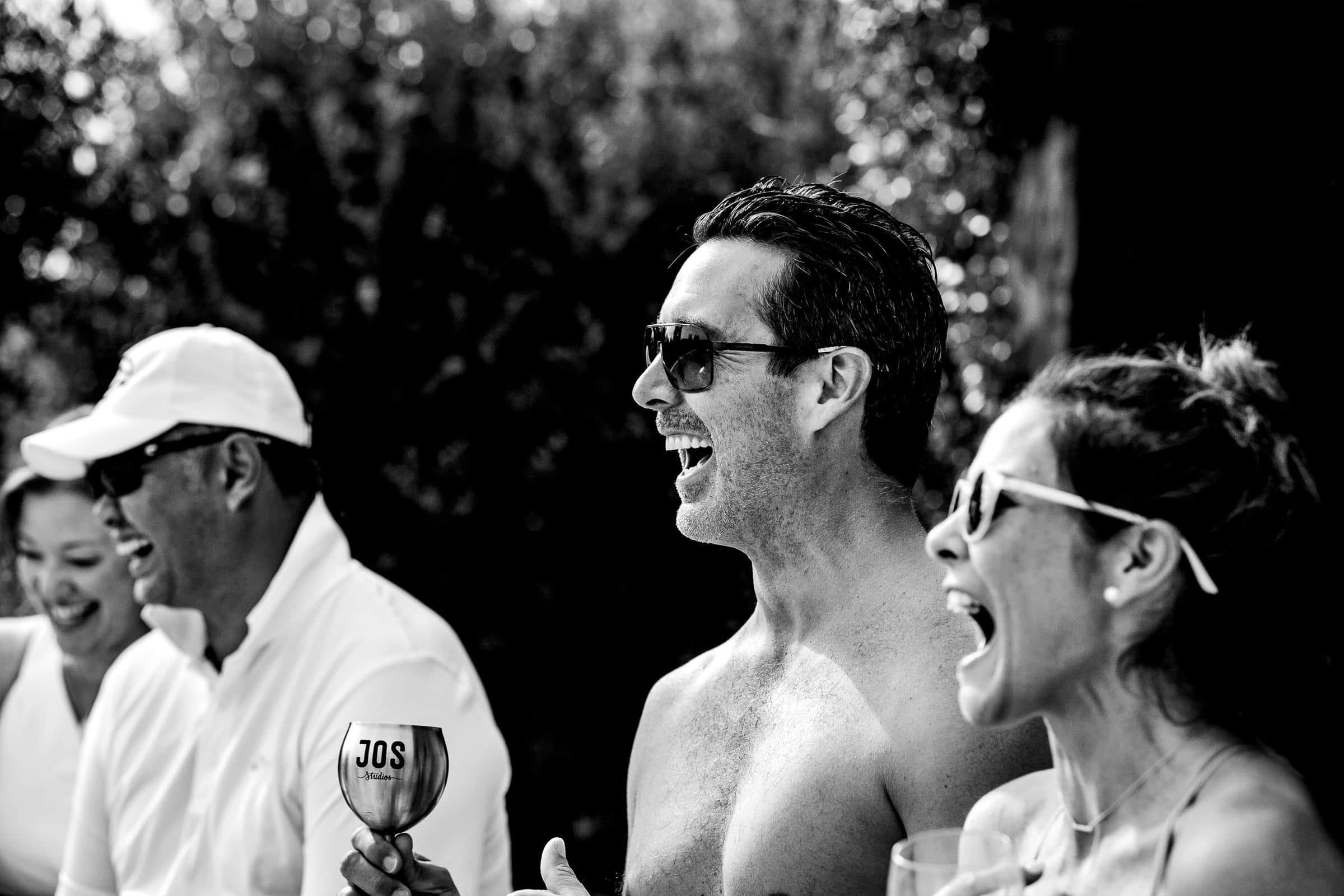 Guest laughing together at a pool party during a Villa Tre Grazie wedding celebration near Todi, Italy.
