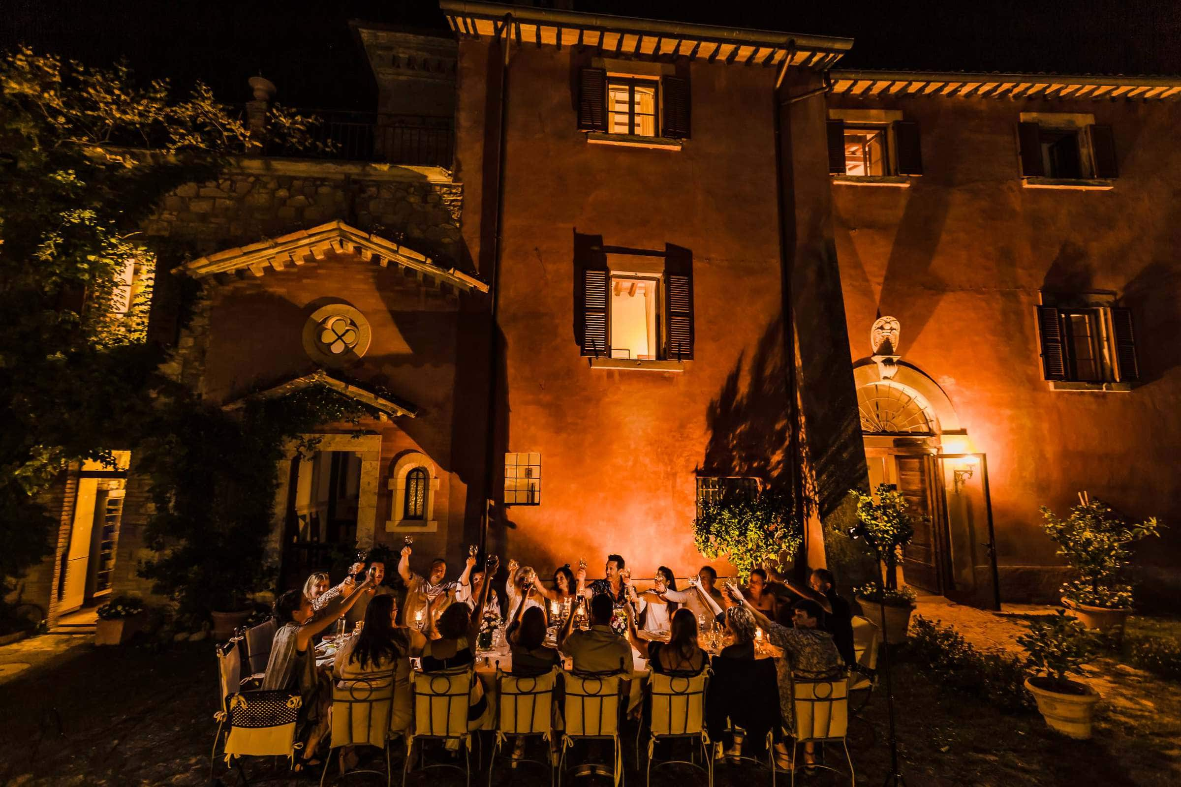 Guests enjoying a reception dinner during a Villa Tre Grazie wedding celebration near Todi, Italy.