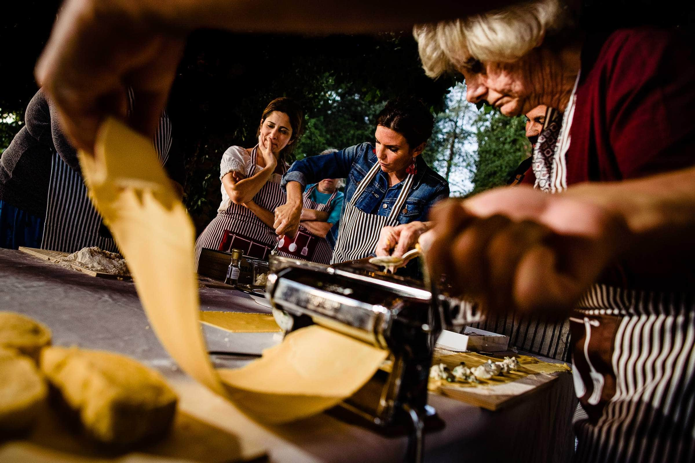 Bride, groom and guests enjoying a day making pasta and drinking wine in a nearby village during their Villa Tre Grazie wedding celebration near Todi, Italy.