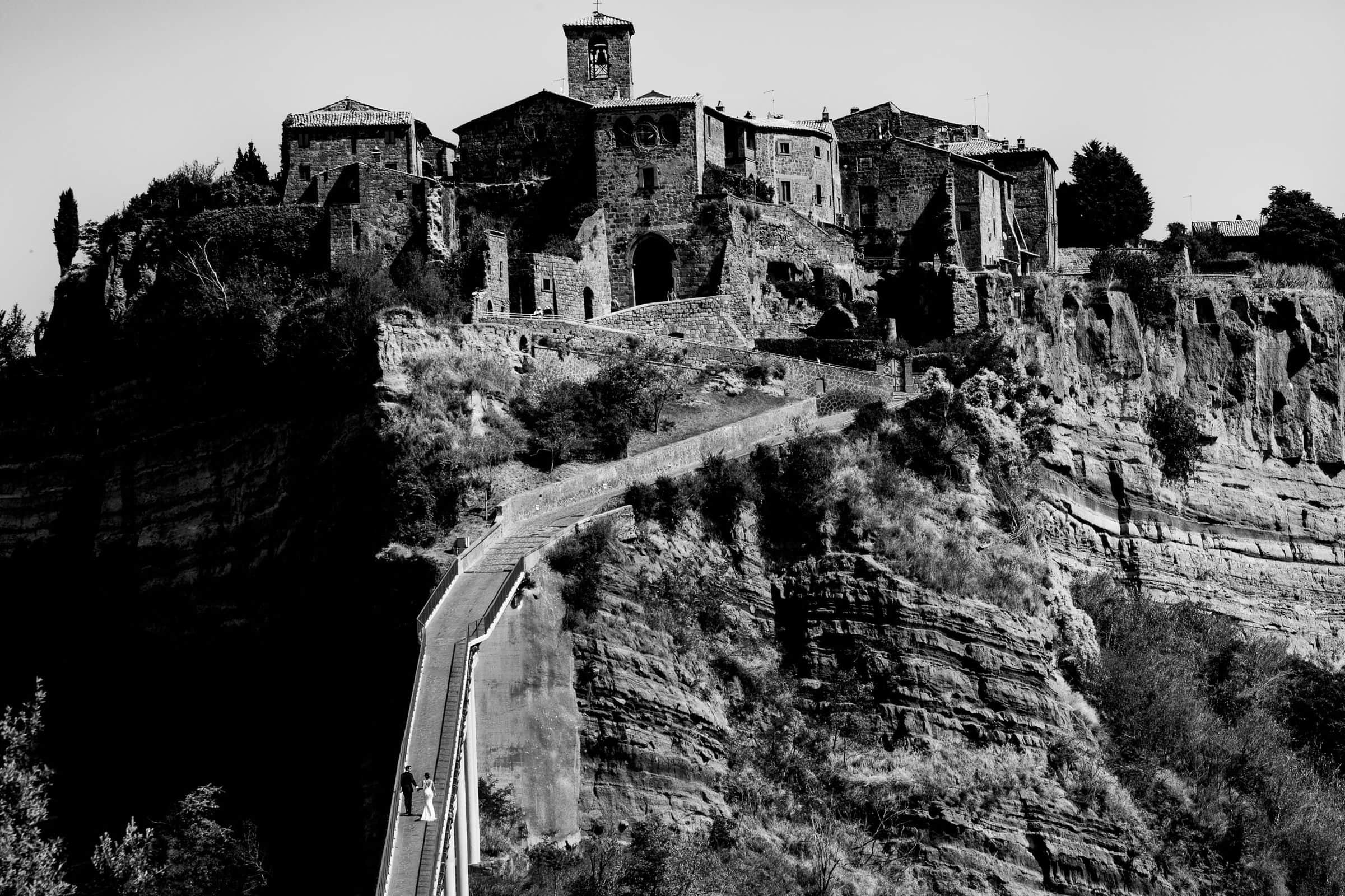 Bride and Groom walking up the trail into civita di bagnoregio in Italy for their wedding