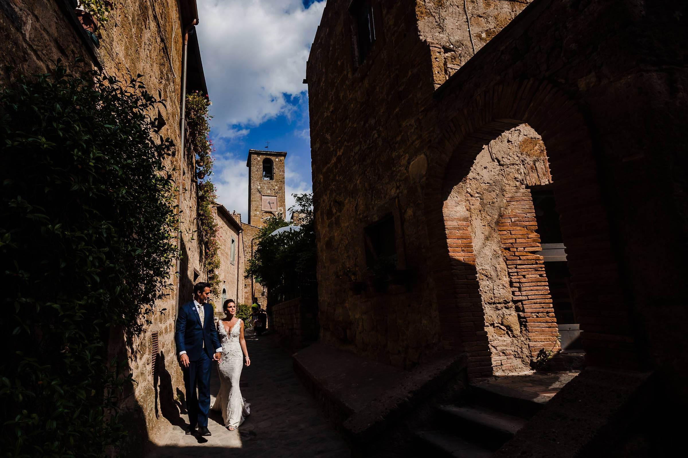 Bride and Groom walking through backstreets into civita di bagnoregio in Italy before their Villa Tre Grazie wedding celebration