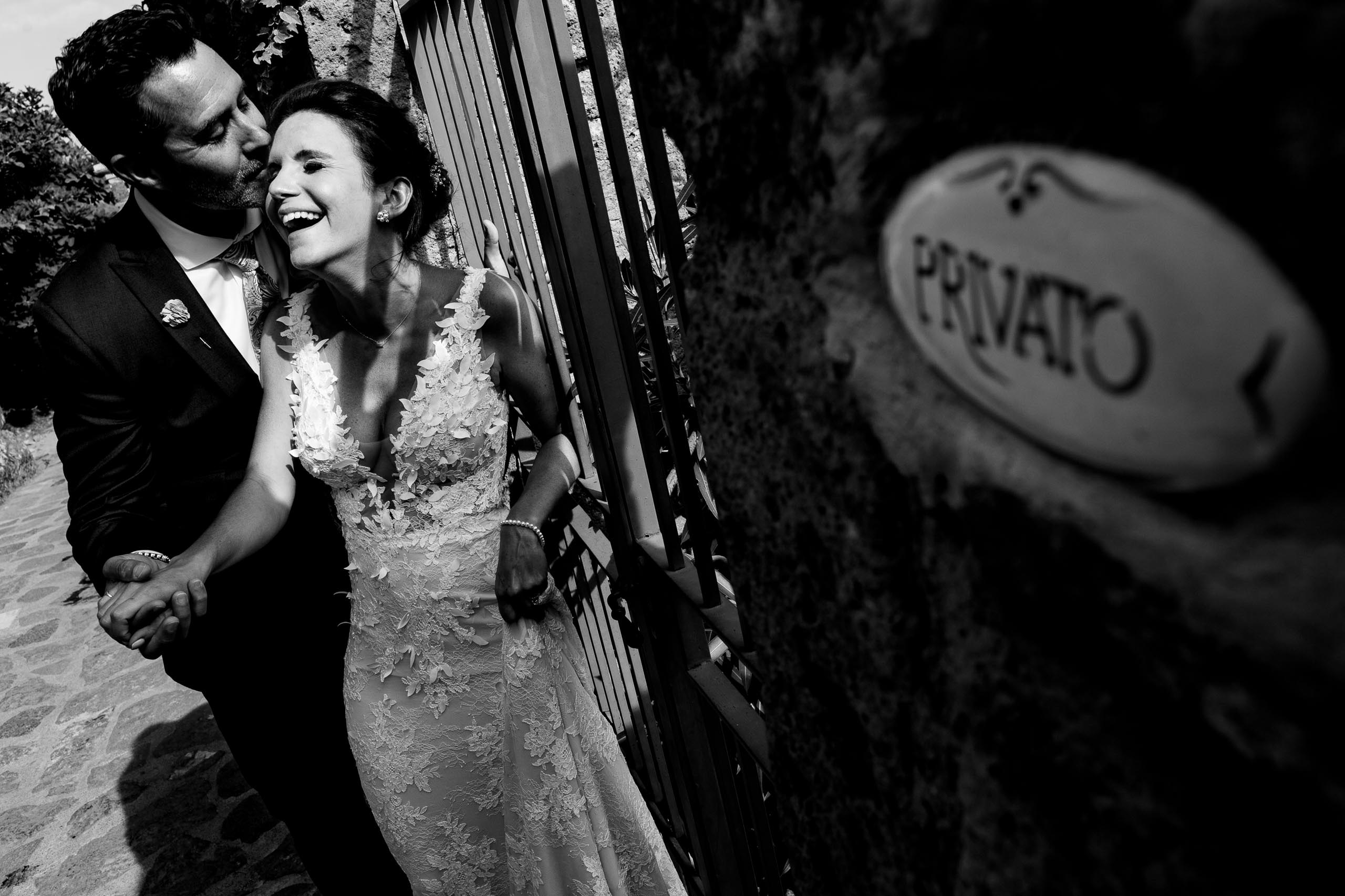 Bride and Groom laughing together in the backstreets of civita di bagnoregio in Italy before their Villa Tre Grazie wedding celebration