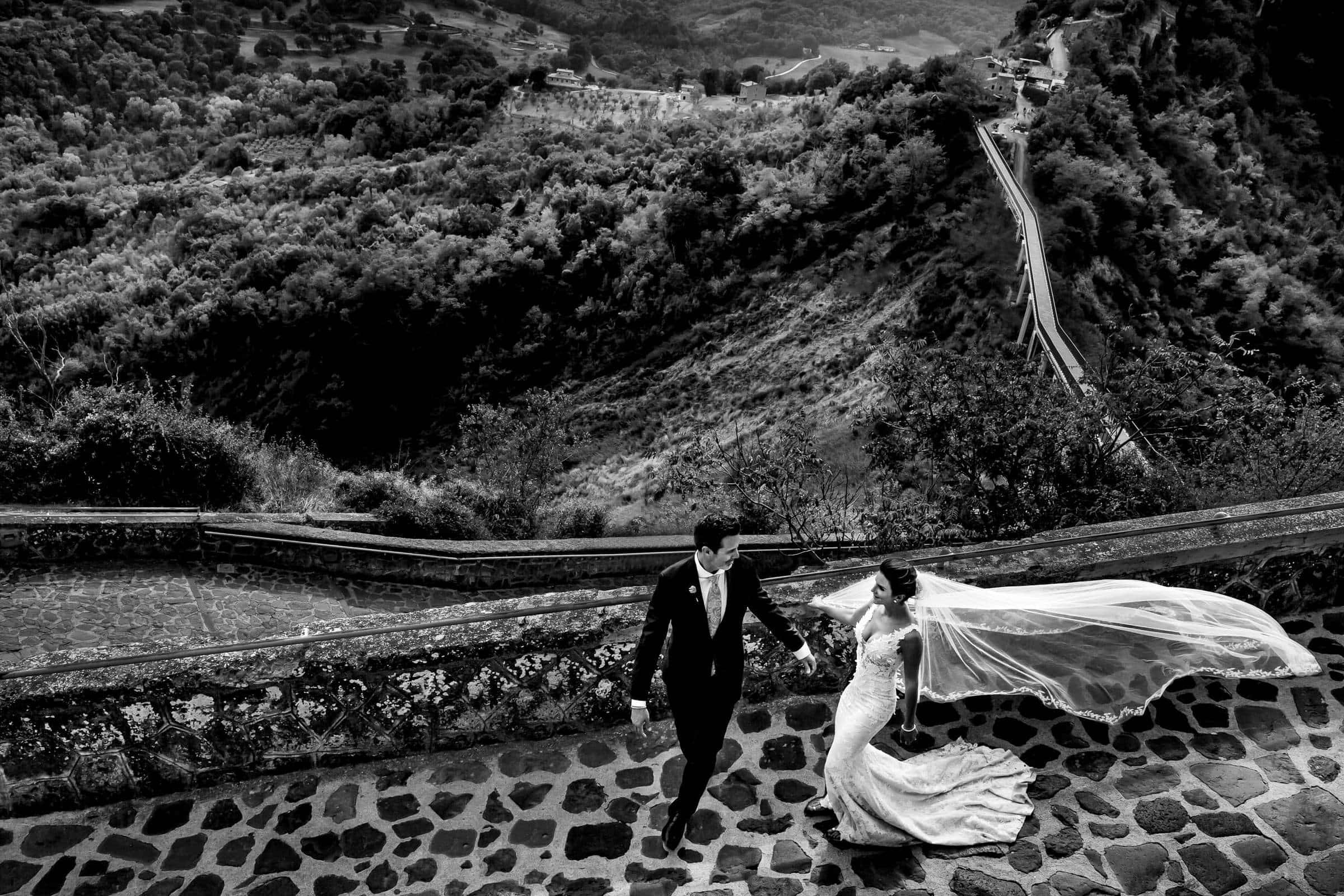 Bride and Groom walking down the trail outside civita di bagnoregio in Italy for their wedding