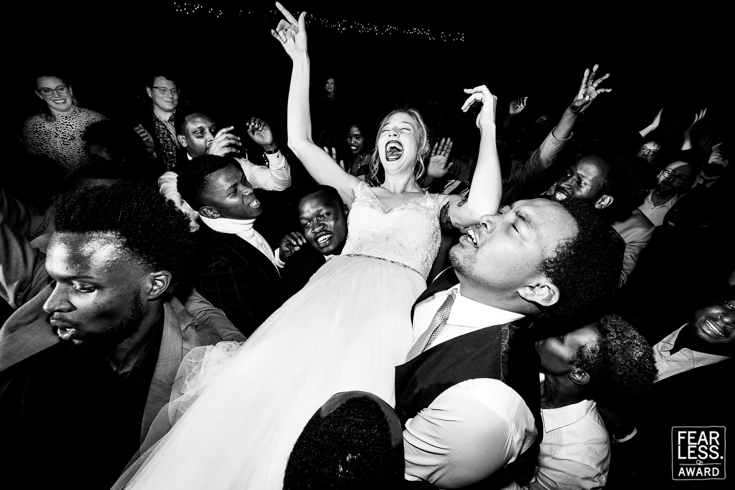 Fearless Photographers Award winning photo of a bride being held up by family and friends during their dance party at their Timberline Lodge wedding on Mt Hood in Oregon