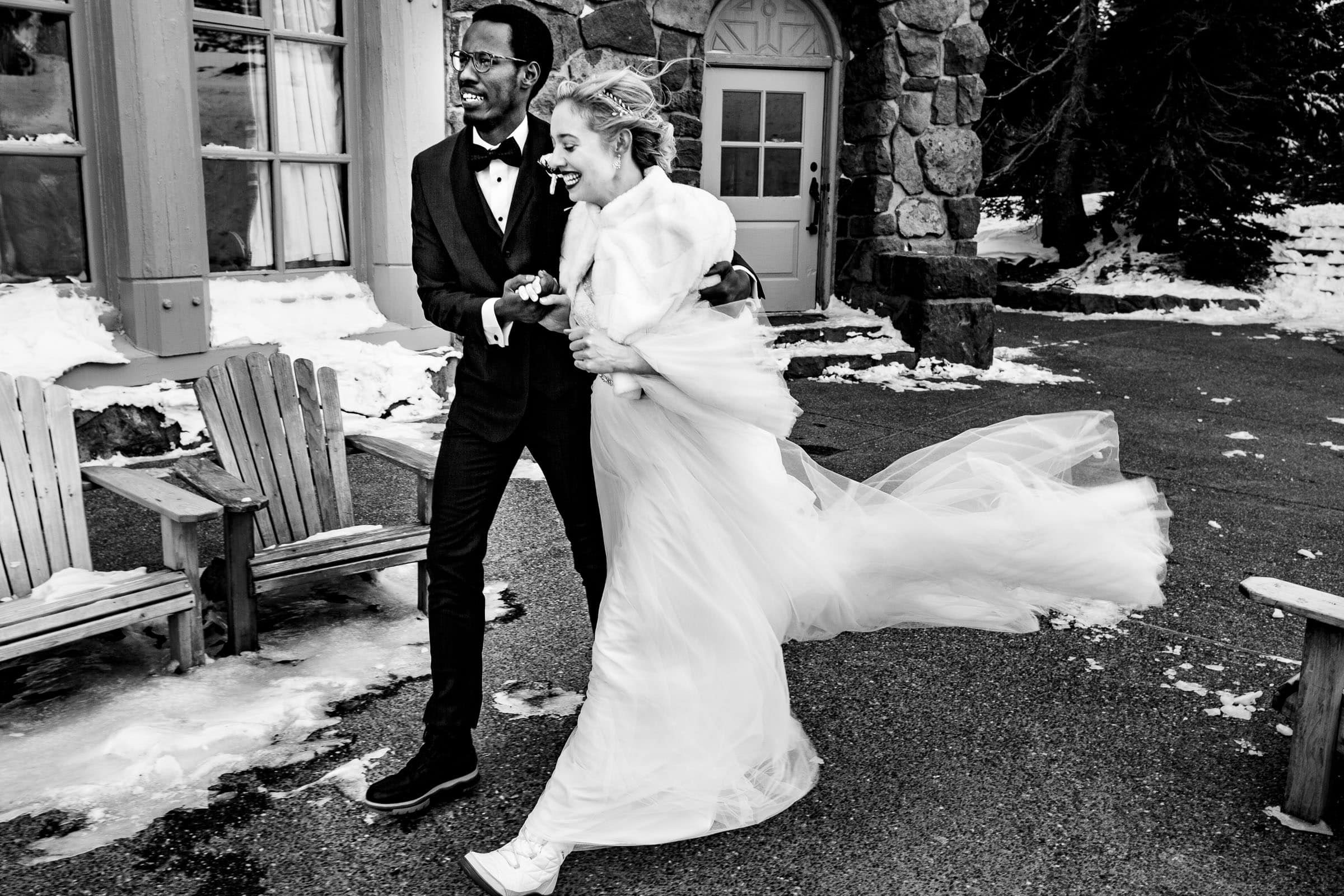 Bride and groom walking in wind outside before their Timberline Lodge Wedding ceremony in the Ravens Nest