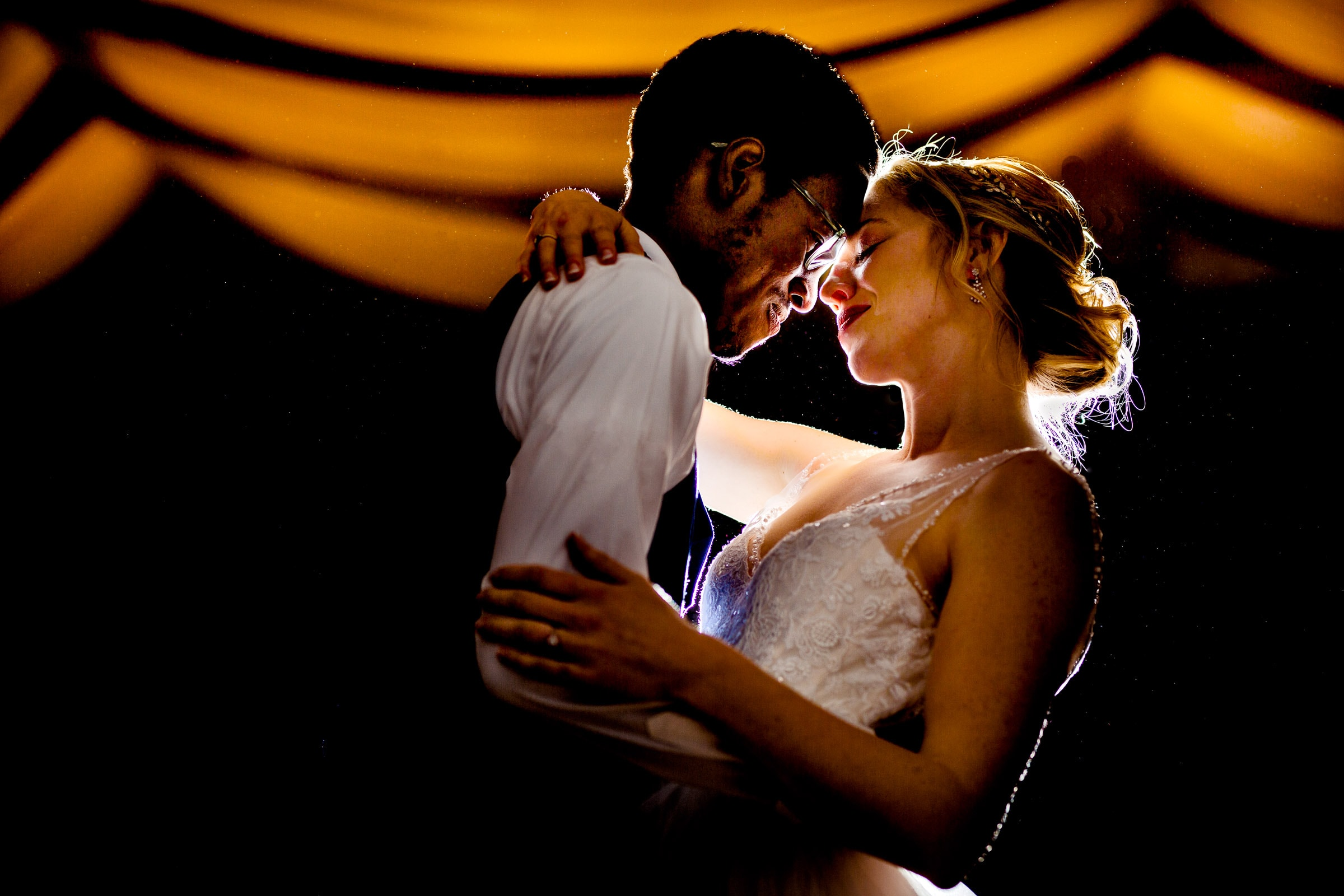 bride and groom first dance with beautiful light at their Timberline Loge Wedding reception