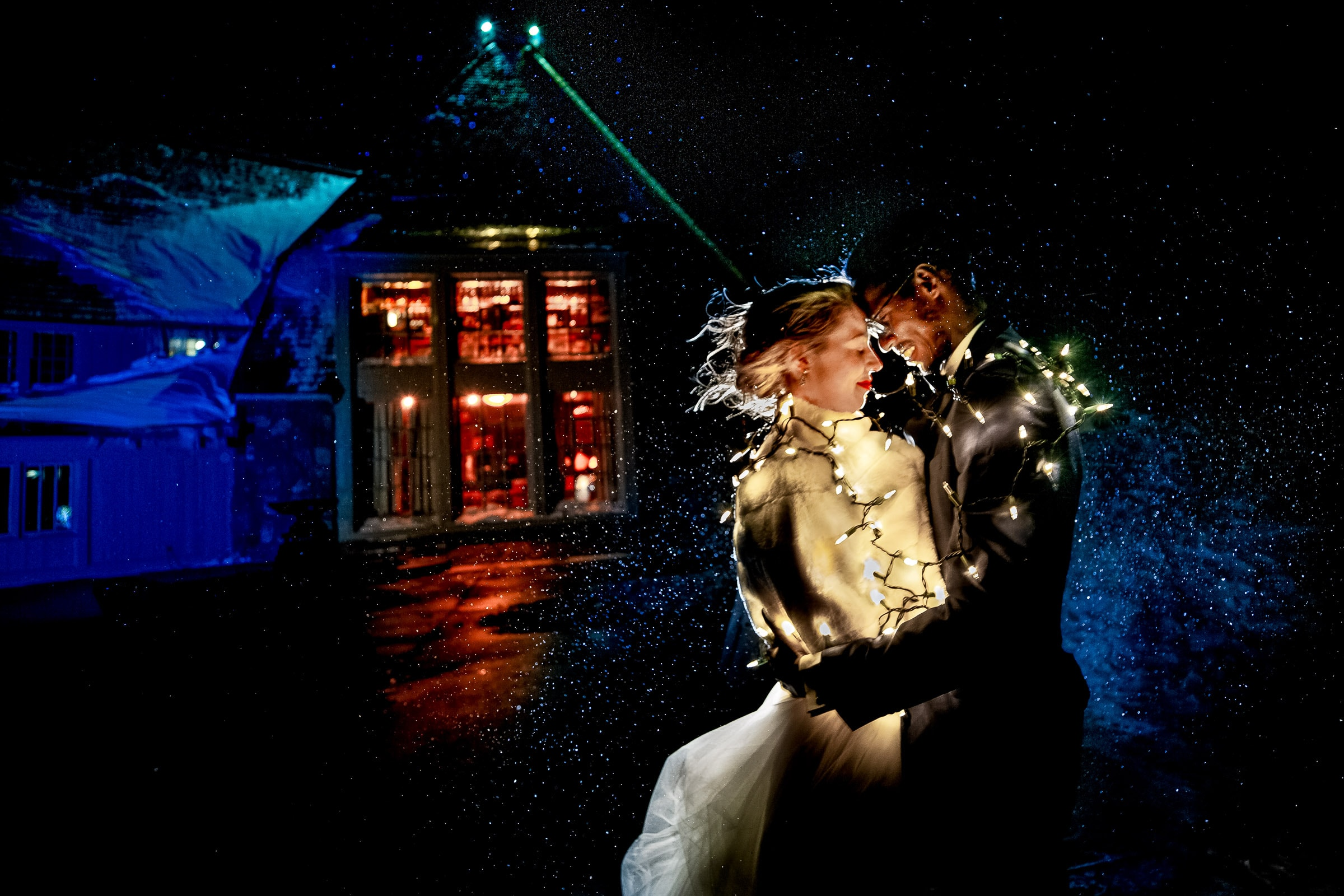 Bride and groom portrait with snow flying everywhere at their Timberline Lodge Wedding reception just outside with the lodge in the background